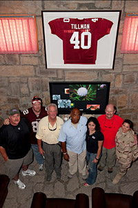 NFL coaches pose with workers below a framed Pat Tillman NFL jersey at the Pat Tillman USO Center at Bagram Air Base in Afghanistan. (USO Photo by Fred Greaves)