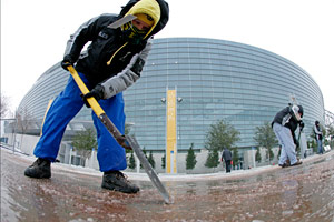 Freezing temperatures and an ice storm Tuesday necessitated workers, including Yvette Hamby, clearing a path to Cowboys Stadium for Super Bowl XLV Media Day.