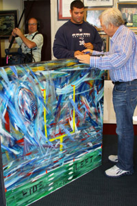 Eric Kattani shows off his painting to Patriots owner Robert Kraft.