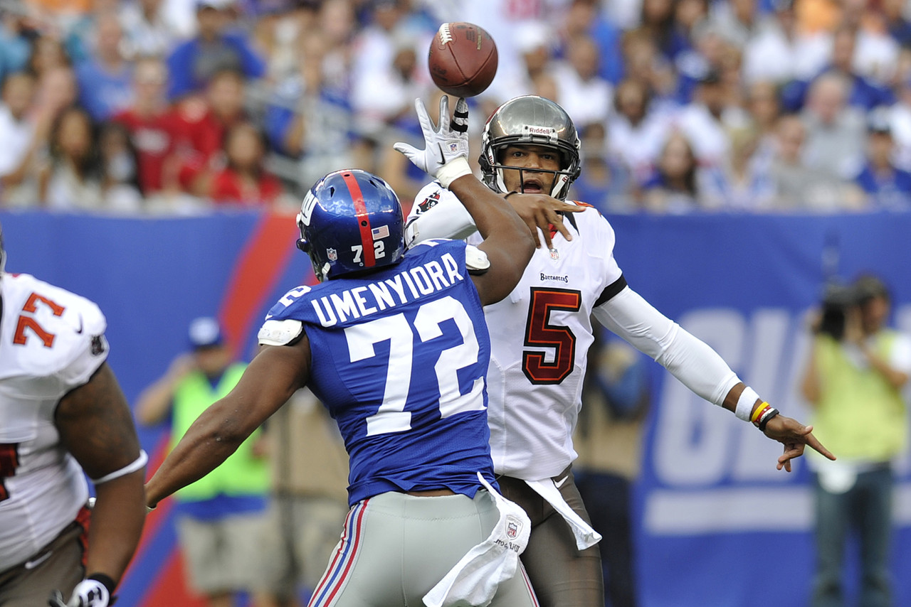 Tampa Bay Buccaneers quarterback Josh Freeman passes over New York Giants defensive end Osi Umenyiora. (AP Photo/Bill Kostroun)