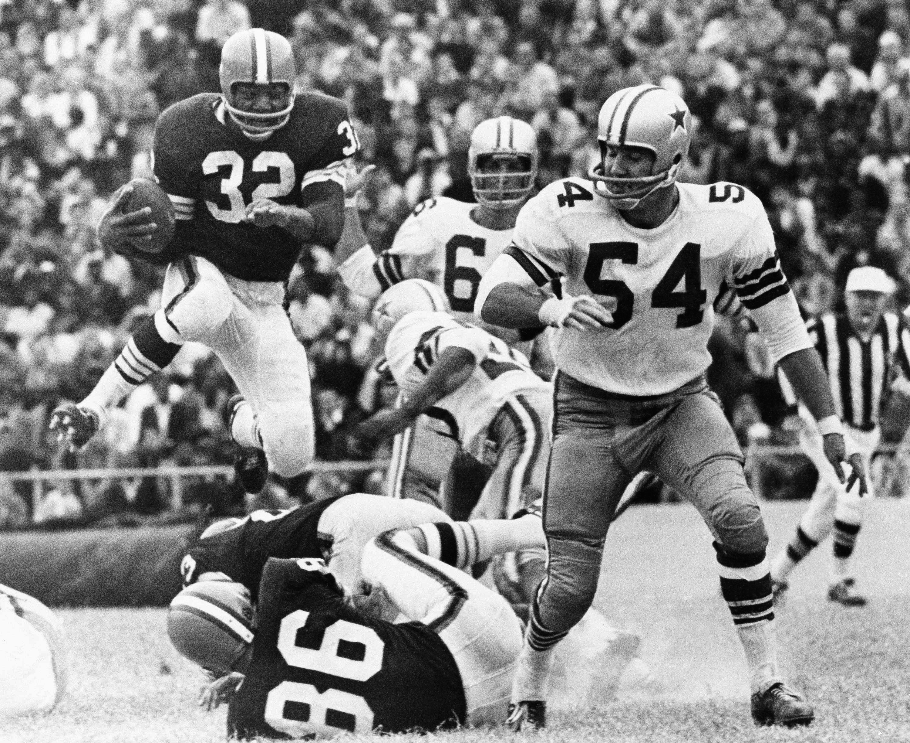 Cleveland Browns fullback, Jim Brown leaps for a gain over right tackle and fellow player Gary Collins (86) in third quarter, in their game with the Dallas Cowboys in Dallas on Oct. 19, 1964. Watching are Cowboy players George Andrie (66) and Chuck Howley (54). (Associated Press)