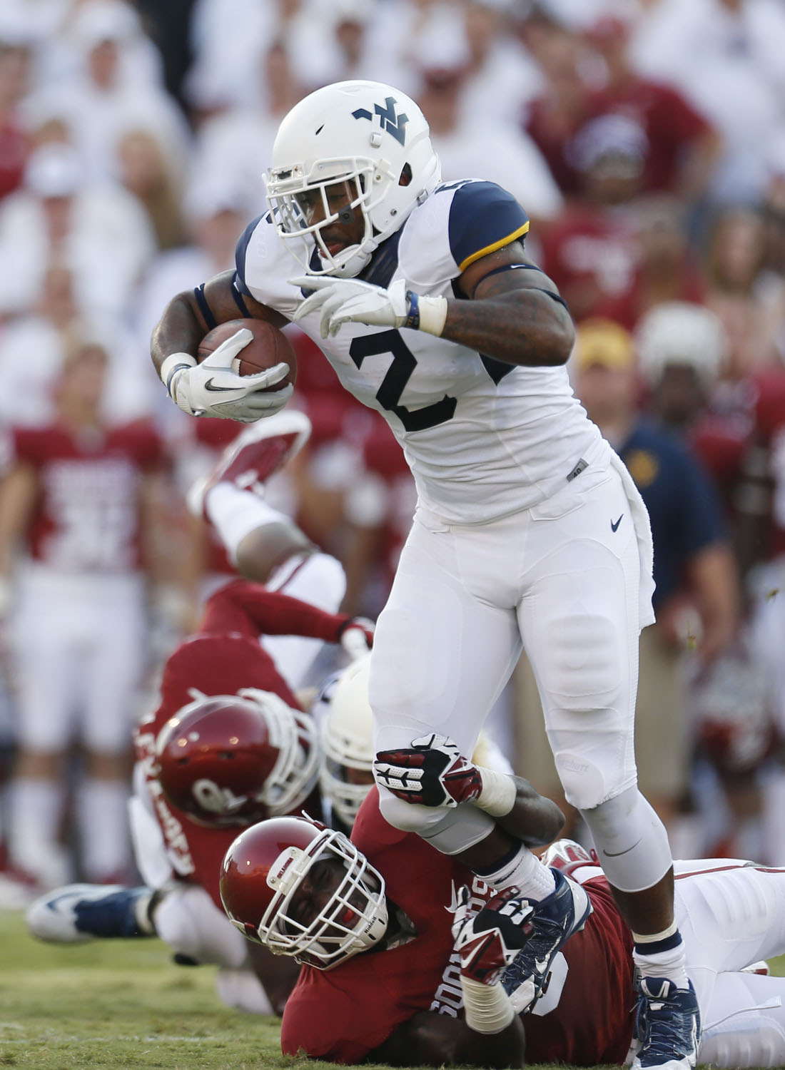 West Virginia running back Dreamius Smith (2) fights off a tackle by Oklahoma defensive back Gabe Lynn (9) and takes off on a 75 yard touchdown run in the first quarter of an NCAA college football game in Norman, Okla., Saturday, Sept. 7, 2013. (AP Photo/Sue Ogrocki)