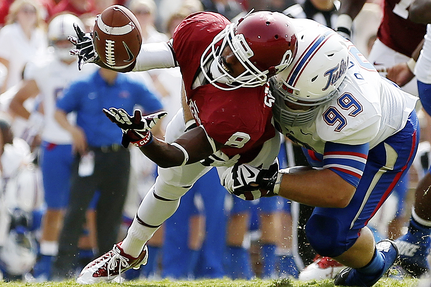 Oklahoma wide receiver Jalen Saunders (8) can't hold onto the pass as he is hit by Tulsa defender Derrick Luetjen. (AP Photo/Sue Ogrocki)
