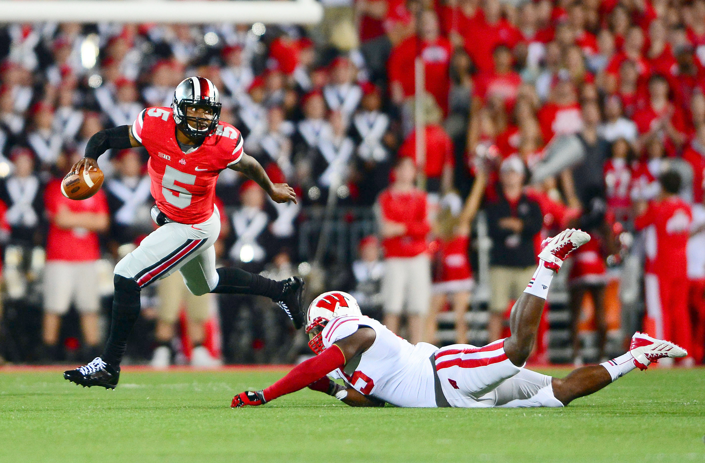 Ohio State Buckeyes quarterback Braxton Miller (5) escapes a Wisconsin Badgers defender during the first quarter at Ohio Stadium. Mandatory Credit: Andrew Weber-USA TODAY Sports