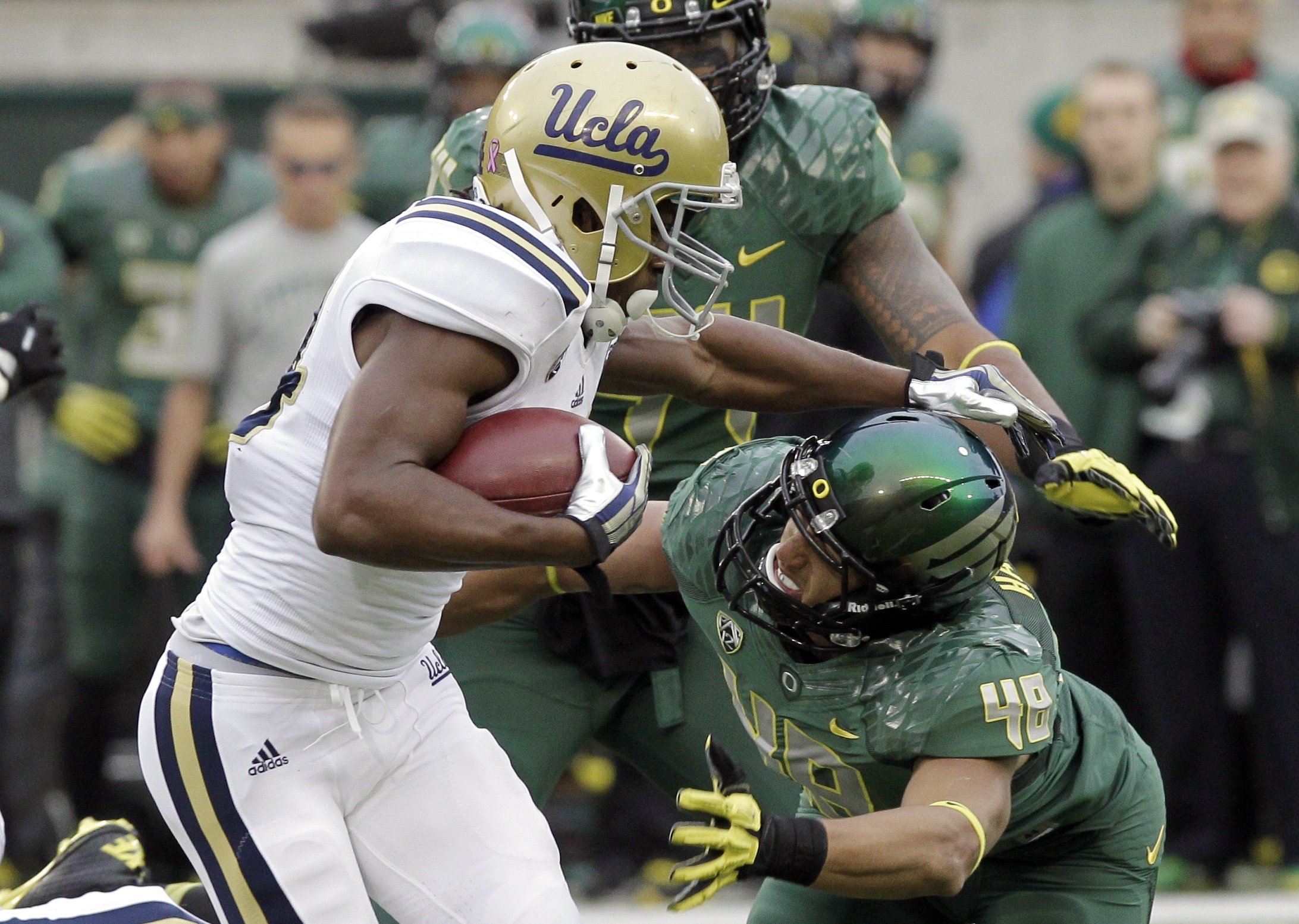 UCLA running back Paul Perkins, left, works for yardage against Oregon defender Rodney Hardrick during the first half of an NCAA college football game in Eugene, Ore., Saturday, Oct. 26, 2013. (AP Photo/Don Ryan)