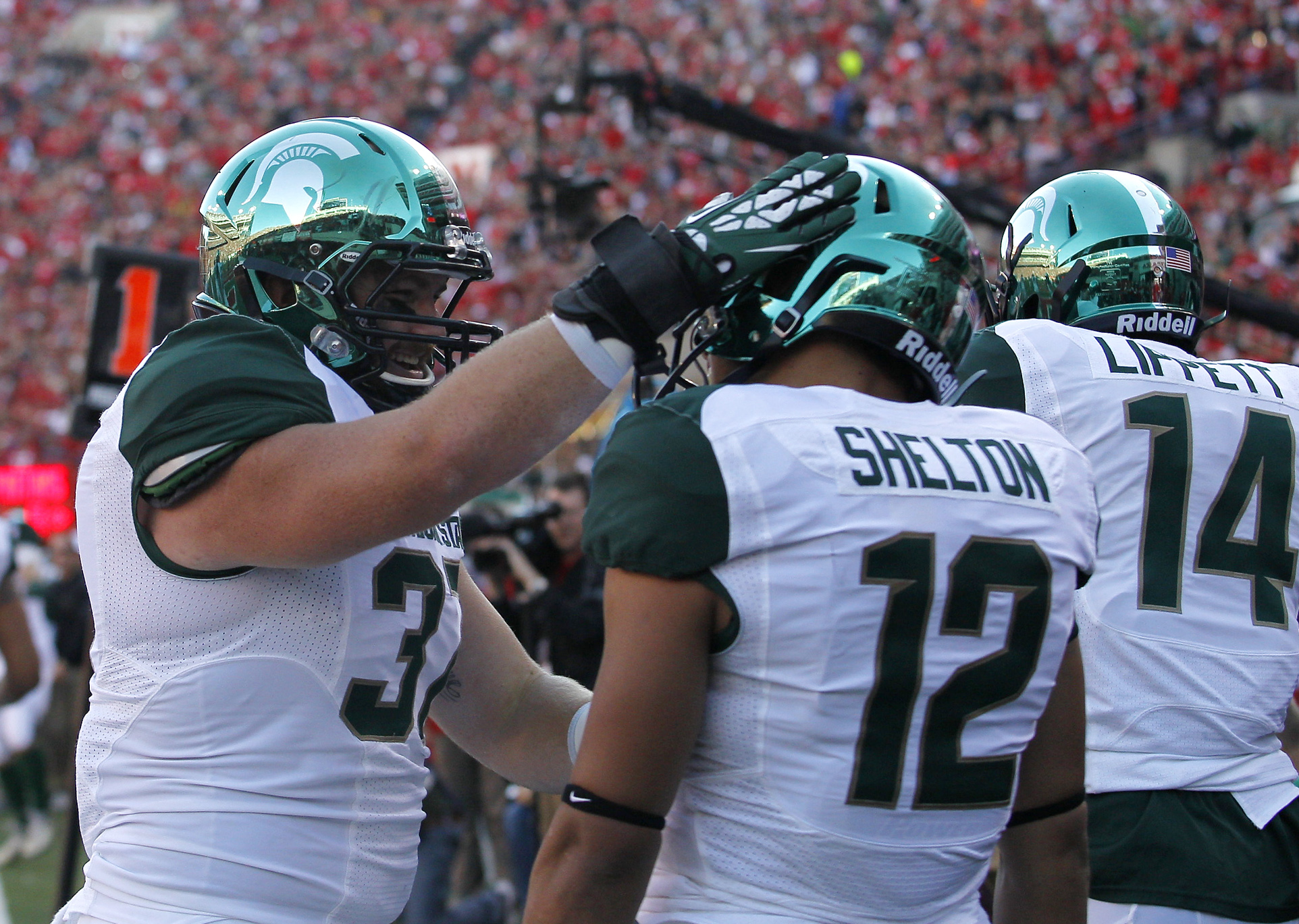 Nov 16, 2013; Lincoln, NE, USA; Michigan State Spartans full back Trevon Pendleton (37) congratulates R.J. Shelton (12) after Shelton's touchdown against the Nebraska Cornhuskers in the first quarter at Memorial Stadium. Mandatory Credit: Bruce Thorson-USA TODAY Sports