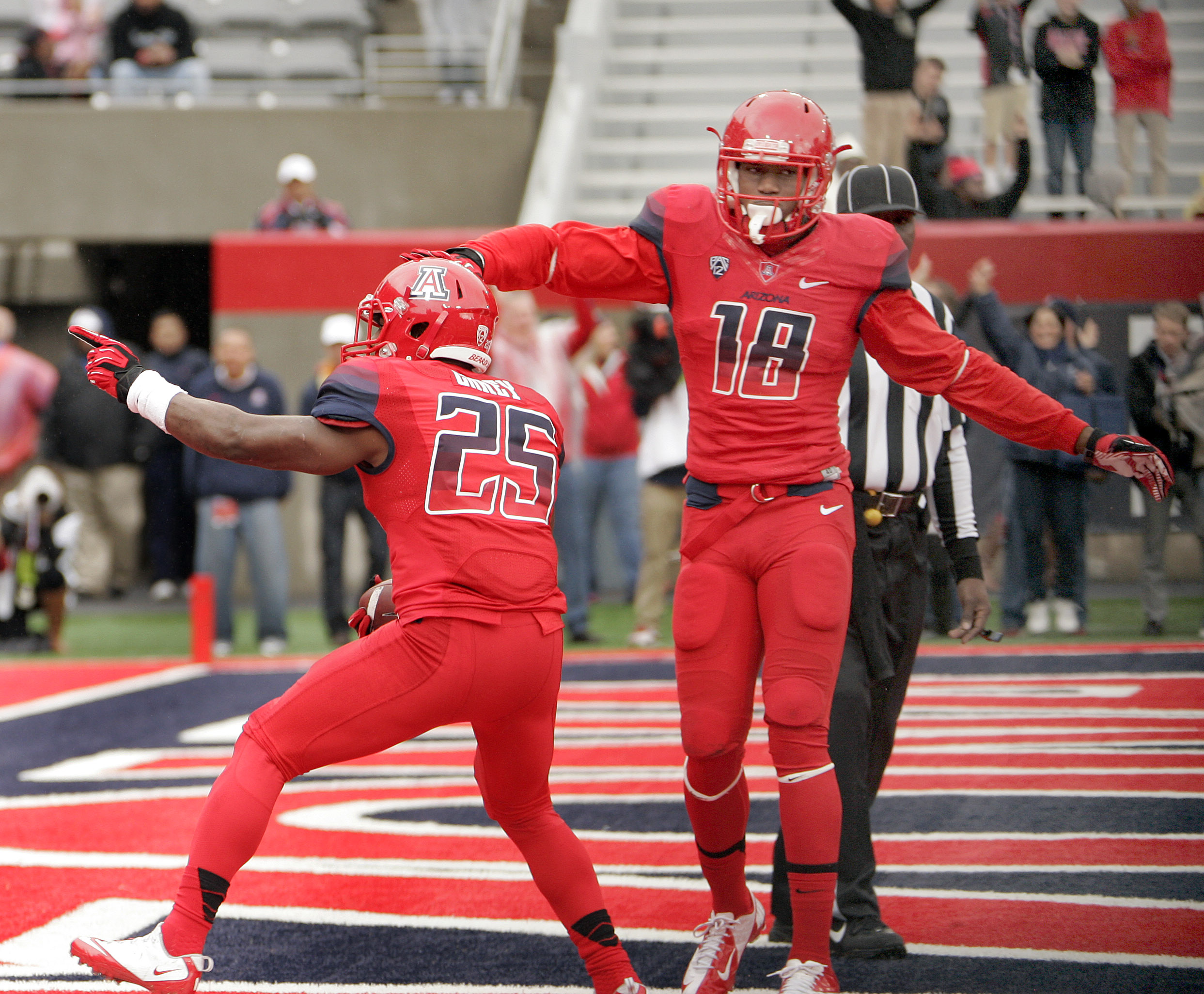 Arizona's Ka'Deem Casey (25) is congratulated by Terrence Miller (18) after scoring a touchdown in the first half of an NCAA college football game against Oregon, Saturday, Nov. 23, 2013 in Tucson, Ariz.  (AP Photo/Wily Low)