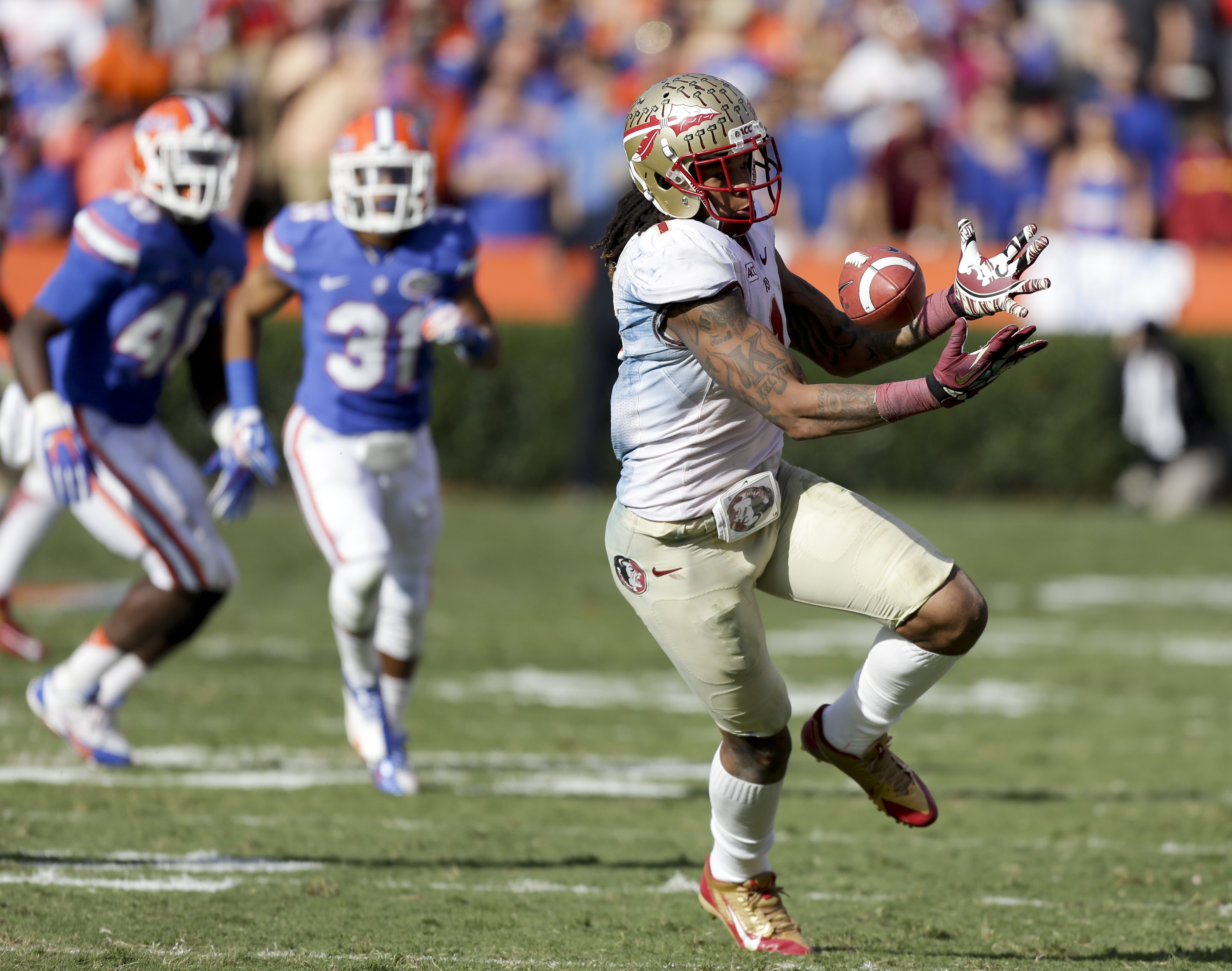 Florida State wide receiver Kelvin Benjamin tries but cannot hang on to a pass in front of Florida defenders William Few (48) and Cody Riggs (31) during the second half of an NCAA college football game in Gainesville, Fla., Saturday, Nov. 30, 2013. Florida State defeated Florida 37-7.(AP Photo/John Raoux)