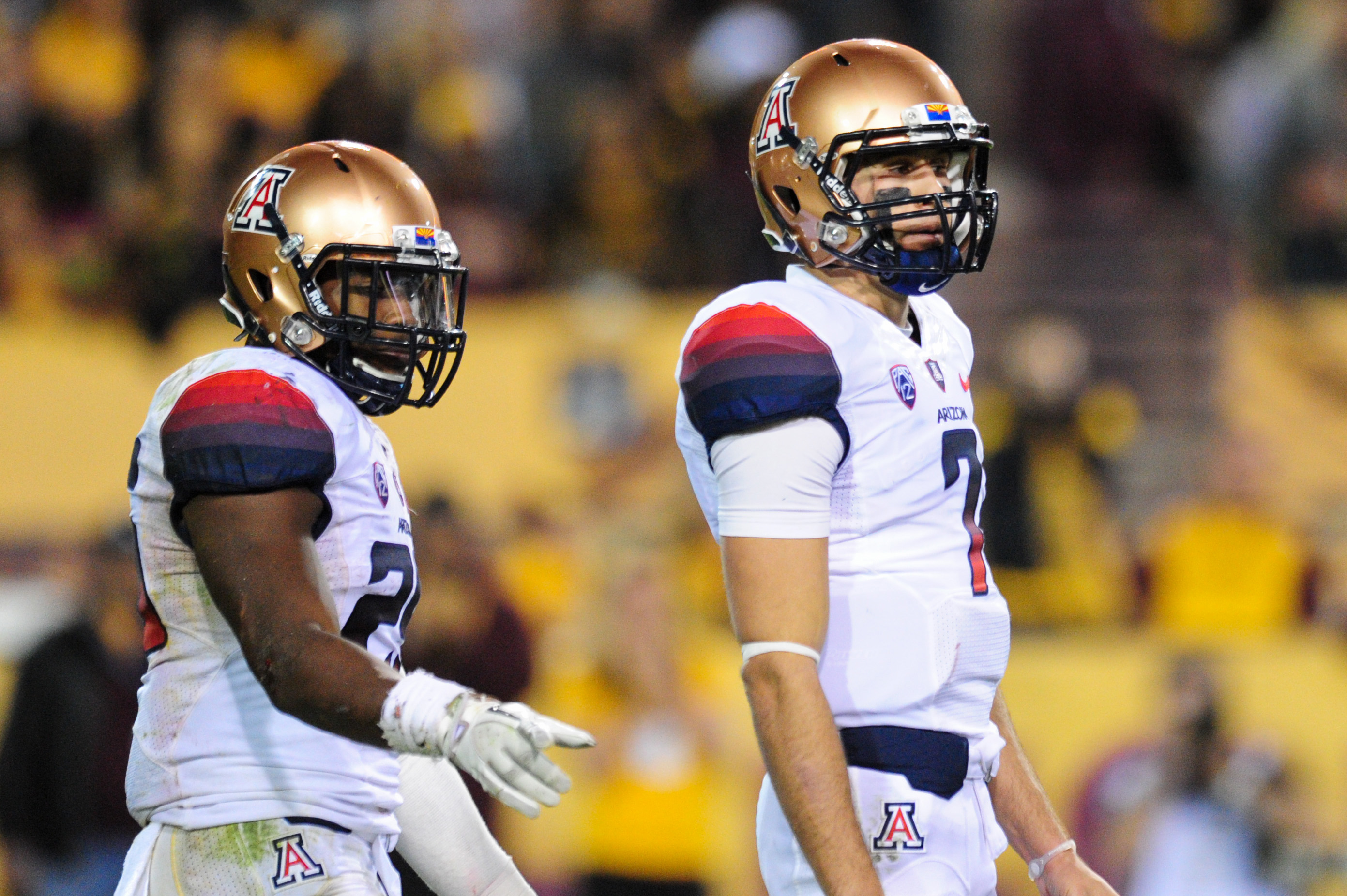 Nov 30, 2013; Tempe, AZ, USA; Arizona Wildcats quarterback B.J. Denker (7) and running back Ka'Deem Carey (25) look on during the first half against the Arizona State Sun Devils in the 87th annual Territorial Cup at Sun Devil Stadium. (Matt Kartozian-USA TODAY Sports)