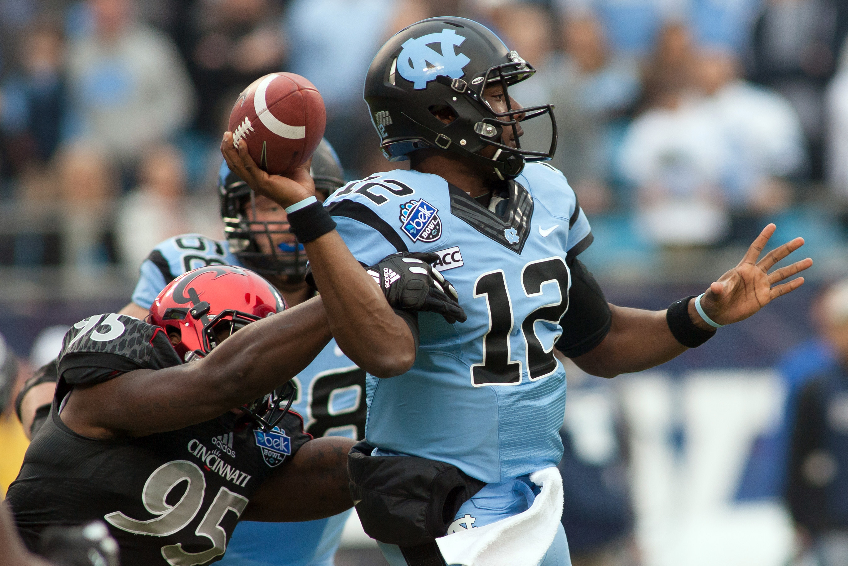 Cincinnati Bearcats defensive end Terrell Hartsfield (95) hits North Carolina Tar Heels quarterback Marquise Williams (12)  as he passes the ball during the first quarter at Bank of America Stadium. (Jeremy Brevard/USA TODAY Sports)