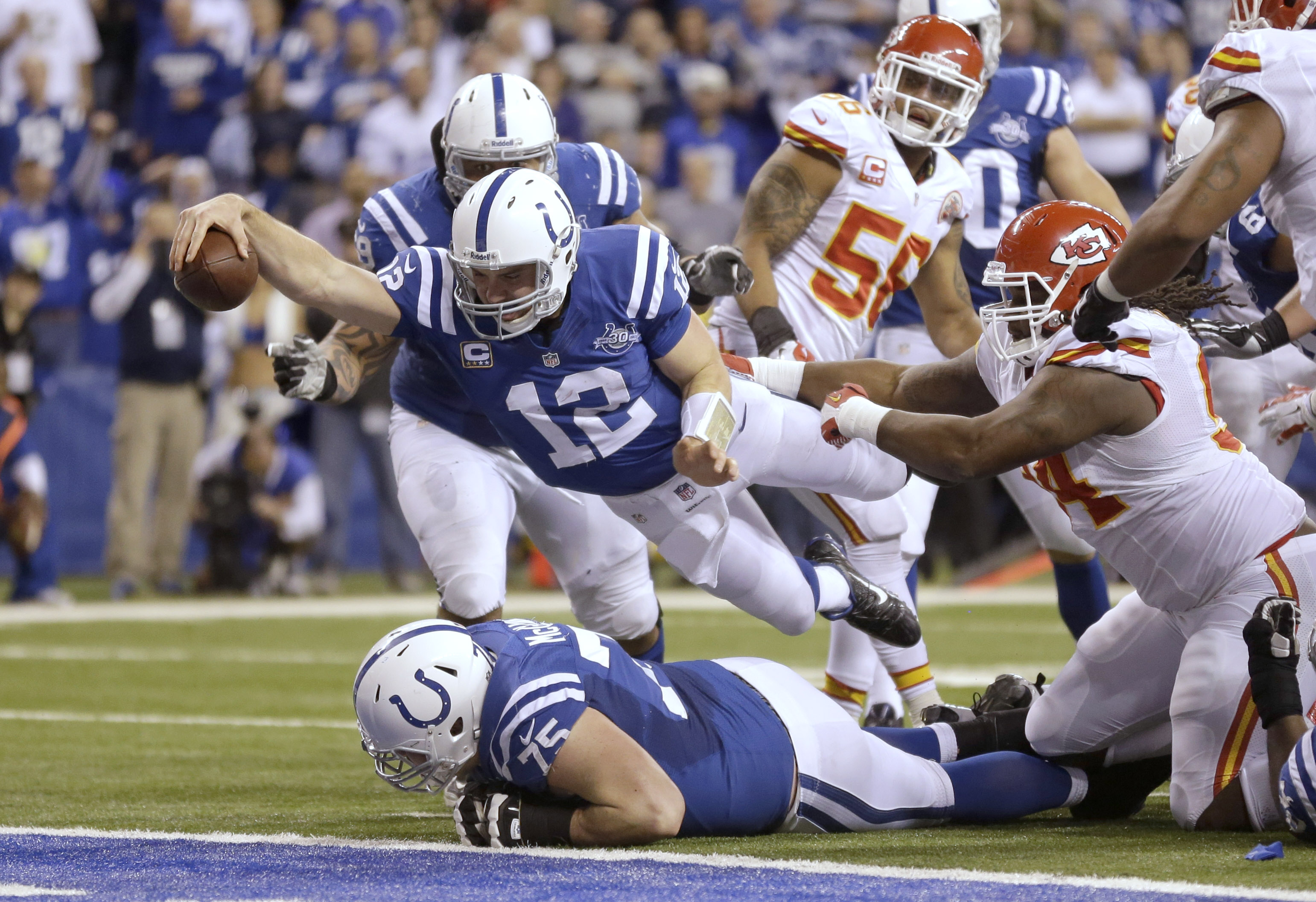 Indianapolis Colts quarterback Andrew Luck (12) dives for a touchdown after recovering a fumble by the Colts' running back Donald Brown (31) during the second half of an NFL wild-card playoff football game against the Kansas City Chiefs Saturday, Jan. 4, 2014, in Indianapolis. (AP Photo/Michael Conroy)