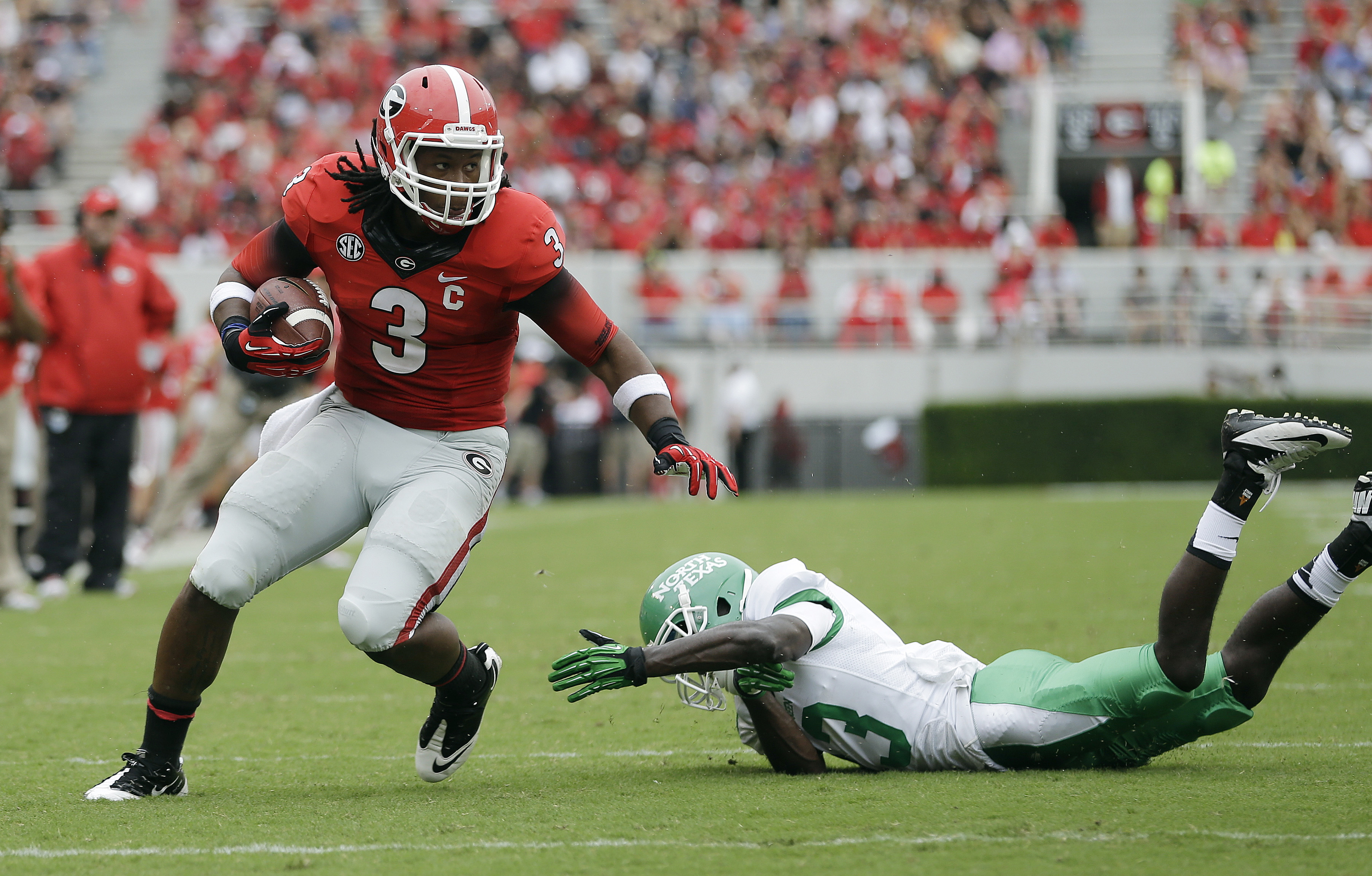 Georgia running back Todd Gurley (3) gets away from North Texas defensive back James Jones (13) as he runs for a touchdown in the first half of an NCAA college football game Saturday, Sept. 21, 2013 in Athens, Ga. (AP Photo/John Bazemore)