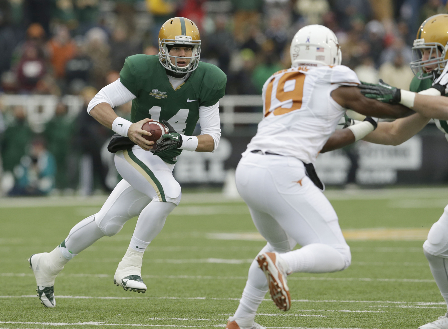 Baylor quarterback Bryce Petty (14) looks for space to run as tight end Jordan Najvar (18) blocks Texas linebacker Peter Jinkens (19) during the first half of an NCAA college football game in Waco, Texas. (LM Otero/Associated Press)