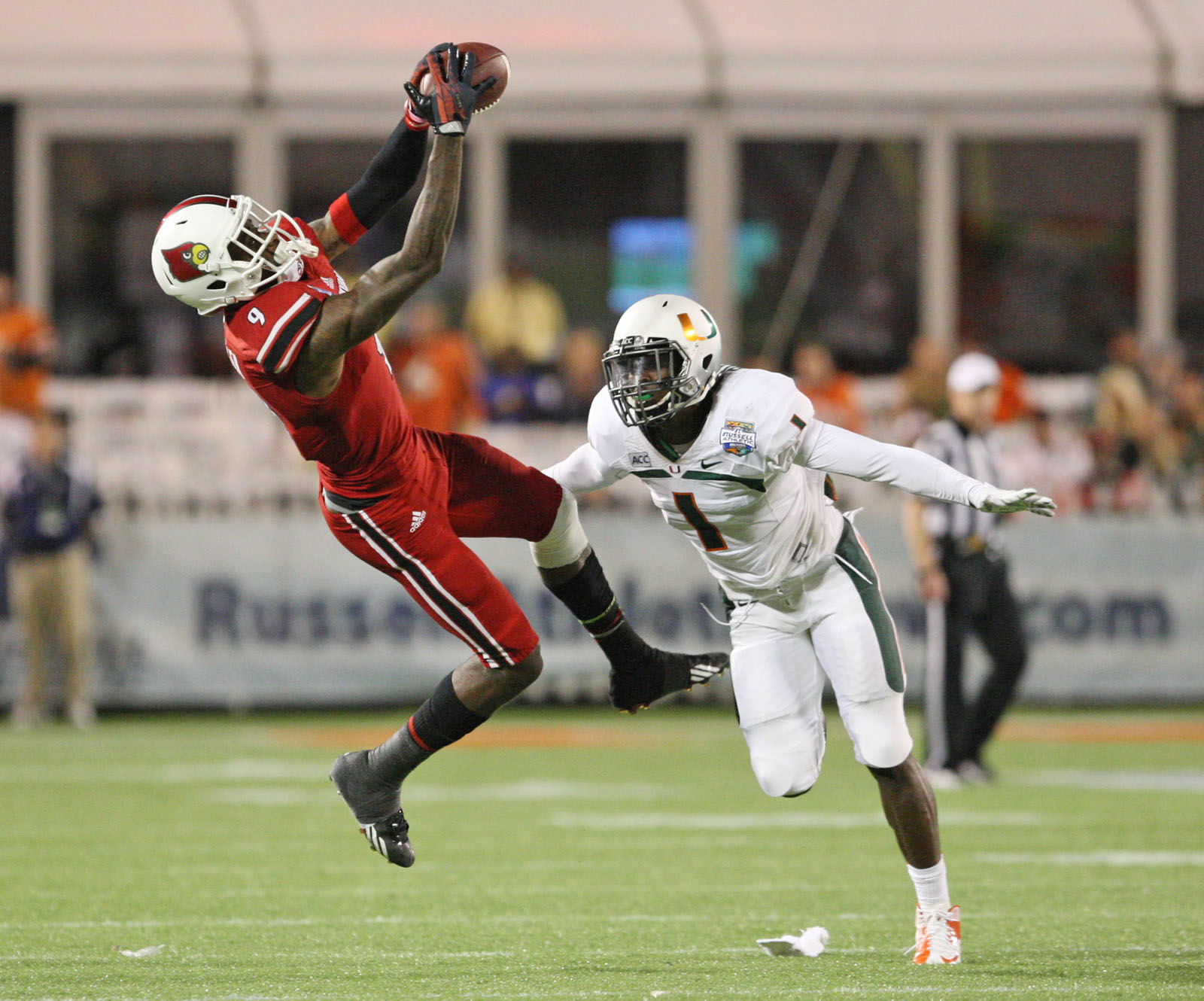 Louisville Cardinals wide receiver DeVante Parker (9) catches a pass while defended by Miami Hurricanes defensive back Artie Burns (1) during the second half of the Russell Athletic Bowl at Florida Citrus Bowl Stadium. (Rob Foldy/USA TODAY Sports)