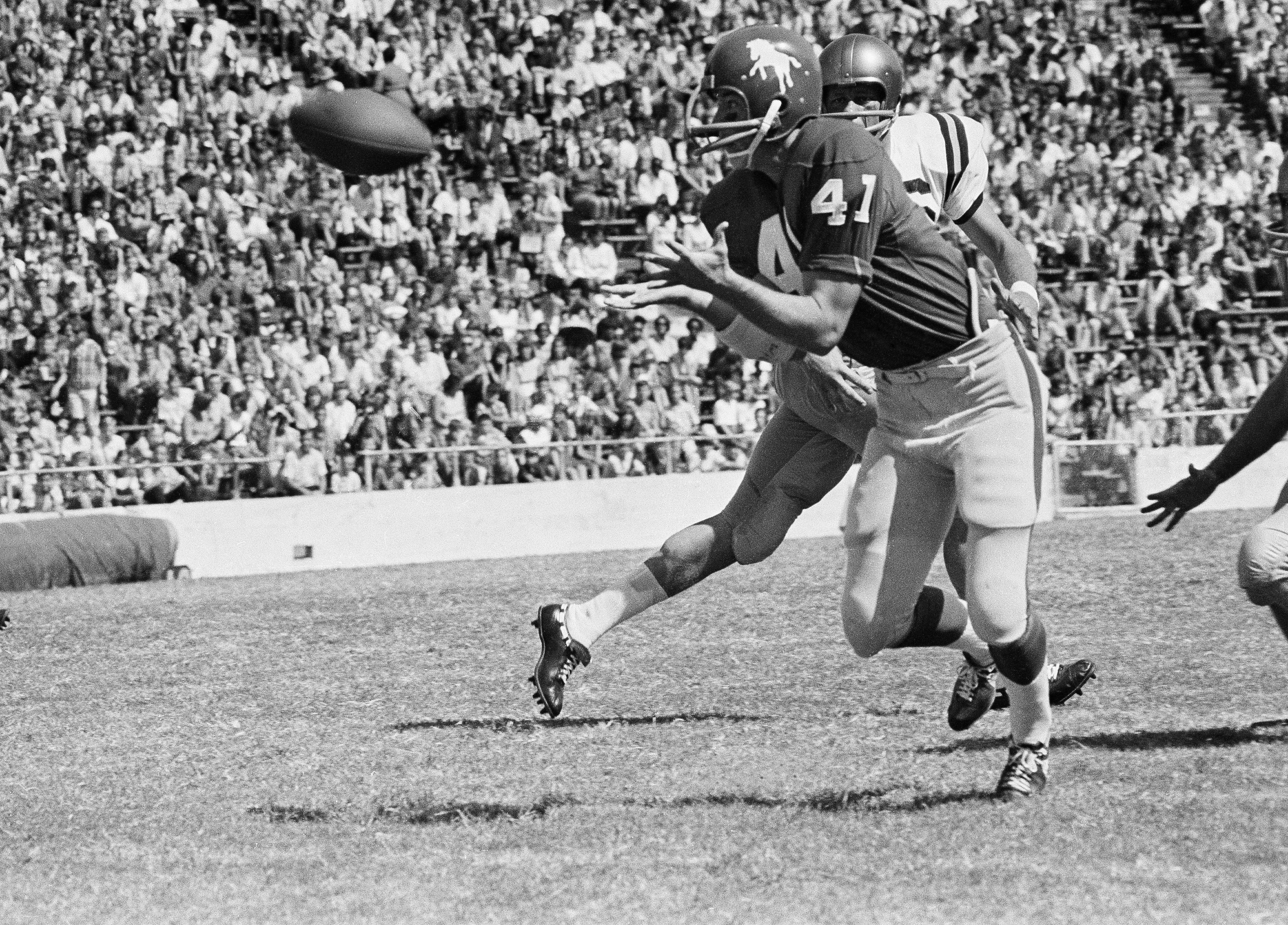 Jerry Wilson (41), SMU defensive safety man, reaches out to pick off a Navy pass intended for Tom Leiser, Navy halfback, during the first quarter of the game, Sept. 24, 1966, Dallas, Texas. Danny Wong, Navy fullback, comes in behind Wilson in an effort to halt the interception. (AP Photo/Robert D. Scott)