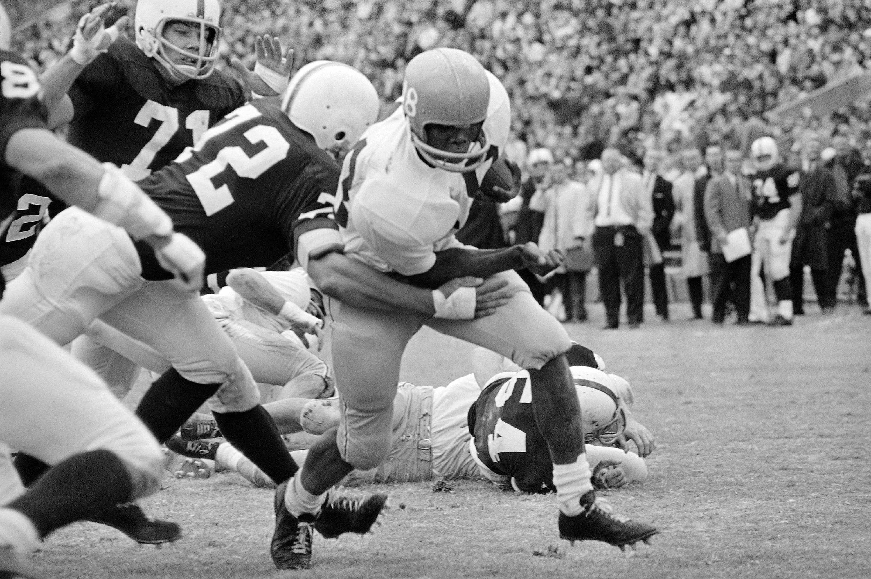 Kansas University's Gale Sayers scores for the Jayhawks in the first quarter of the Kansas-Kansas state game at Manhattan. At left, Kansas State's Ken Nash (72) moves in for the tackle. (AP Photo/William Straeter)