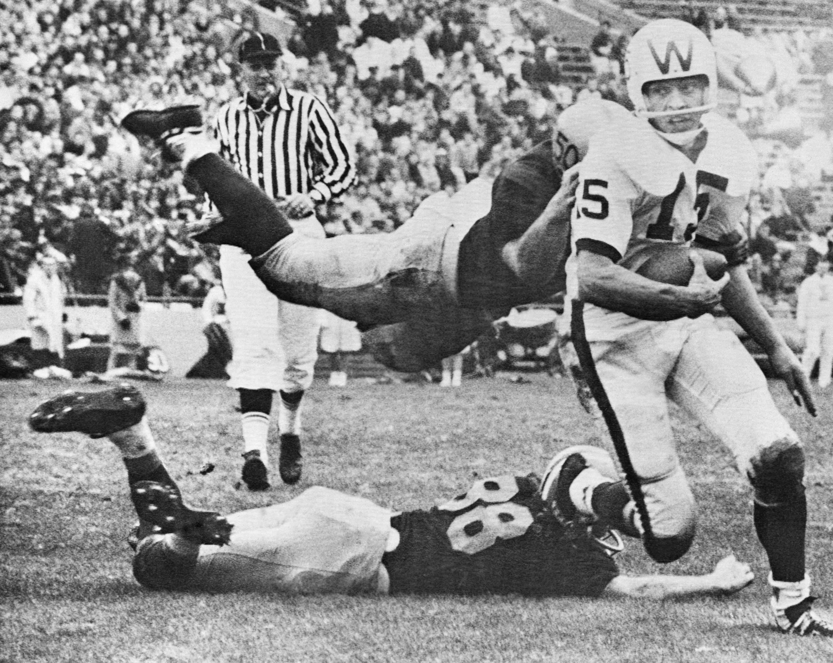 An flying Illinois tackler hits the head of Wisconsin quarterback Ron Vanderkelen (15) and another Illinois man grabs him by the feet as they try to stop him as he runs for a first down in the second quarter, Nov. 17, 1962, Champaign, Ill. Illinois center Dick Butkus is the flying tackler and Illinois and Rich Callaghan is the ground man. (AP Photo/Larry Stoddard)