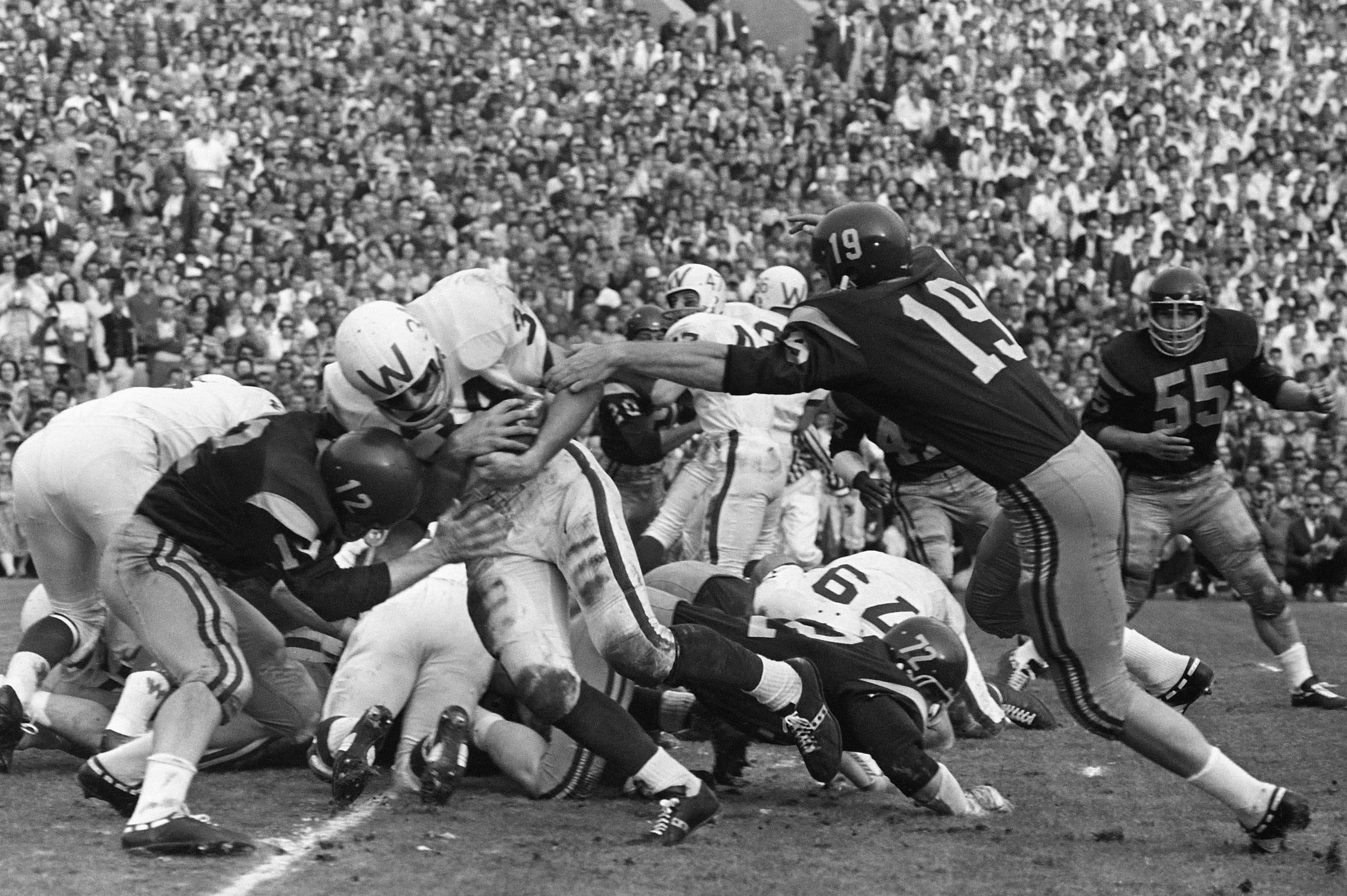 Wisconsin fullback Ralph Kurek (34), smashes off tackle into the end zone to score his teams first touchdown against Southern California while going down to a 42-37 defeat at the Rose Bowl, Jan. 2, 1963, at  Pasadena CA. Kurek takes hand-off from quarterback Ron VanderKelen, and then hit at goal line by USC quarterback Pete Beathard (12) as end Hal Bedsole (19) lunges for his bottom, he shoves Beathard back and scores. (Associated Press)