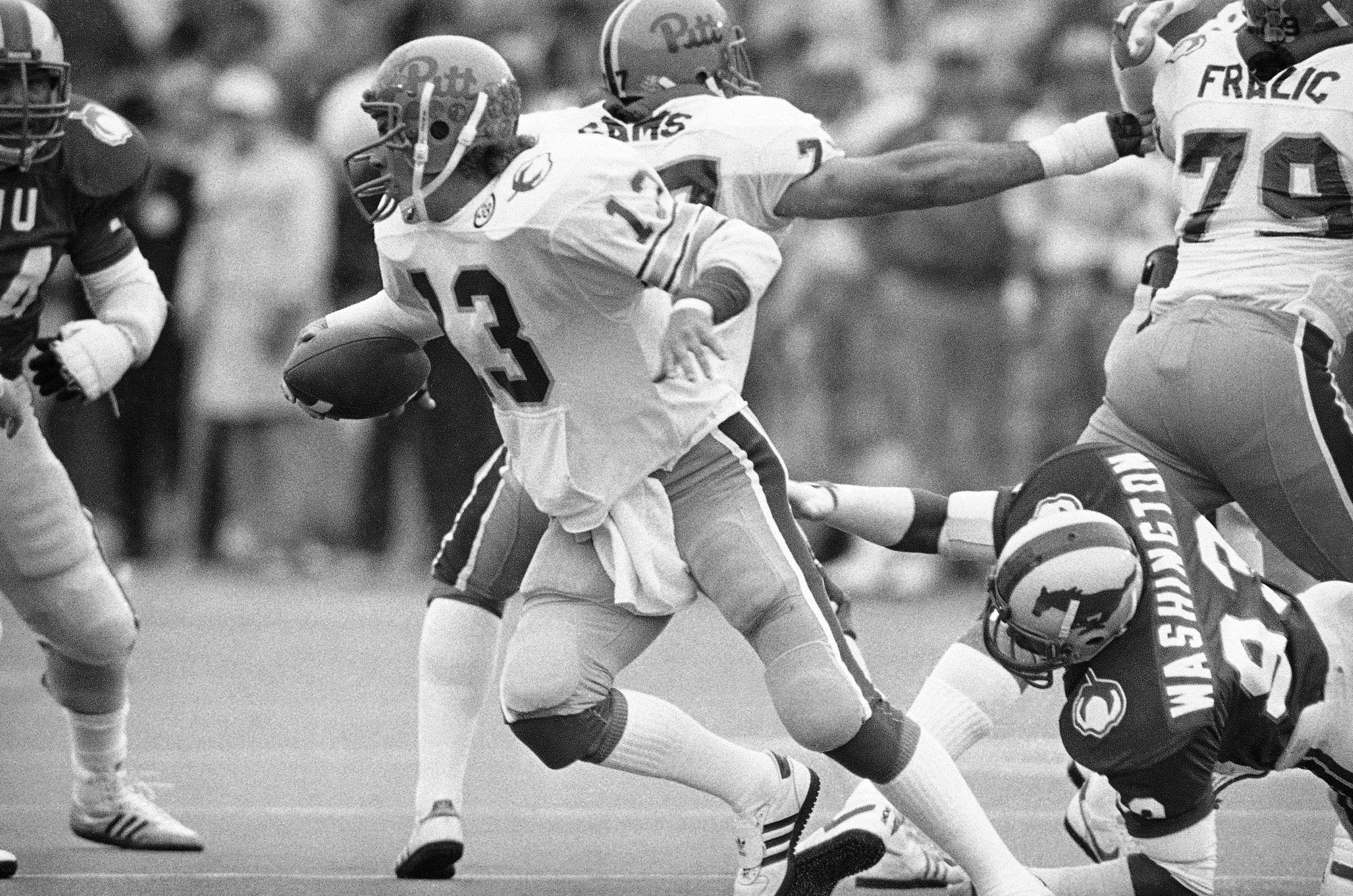 University of Pittsburgh quarterback Dan Marino (13) makes his move to elude the tackle attempt by Southern Methodist University defensive end Russell Washington, right, during first quarter action in the Cotton Bowl, Jan. 1, 1983 in Dallas. Marino gained two yards on the scramble. (AP Photo/Bill Haber)