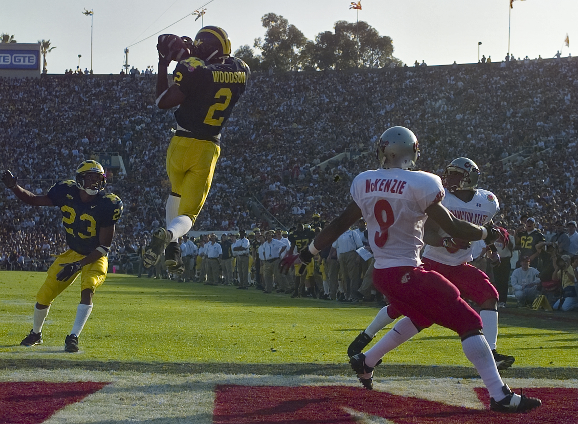 Michigan's cornerback Charles Woodson (2) leaps to make an interception in the end zone in the first half on a pass from Washington State's Ryan Leaf during the 84th Rose Bowl in Pasadena, Calif., Thursday, Jan. 1, 1998. Watching the play are Michigan's William Peterson (23) and Washington States Kevin McKenzie (9). Player at right unidentified. (AP Photo/Mark J. Terrill)