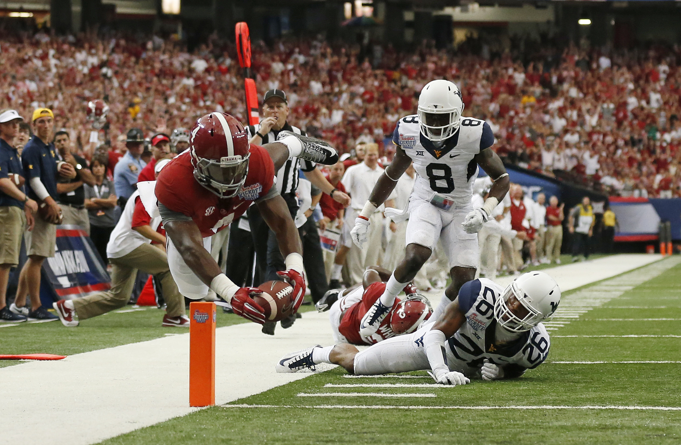 Alabama running back T.J. Yeldon (4) dives into the end zone for a touchdown as West Virginia's Travis Bell (26) and Karl Joseph (8) defend in the first half of an NCAA college football game Saturday, Aug. 30, 2014, in Atlanta.  (AP Photo/Brynn Anderson)