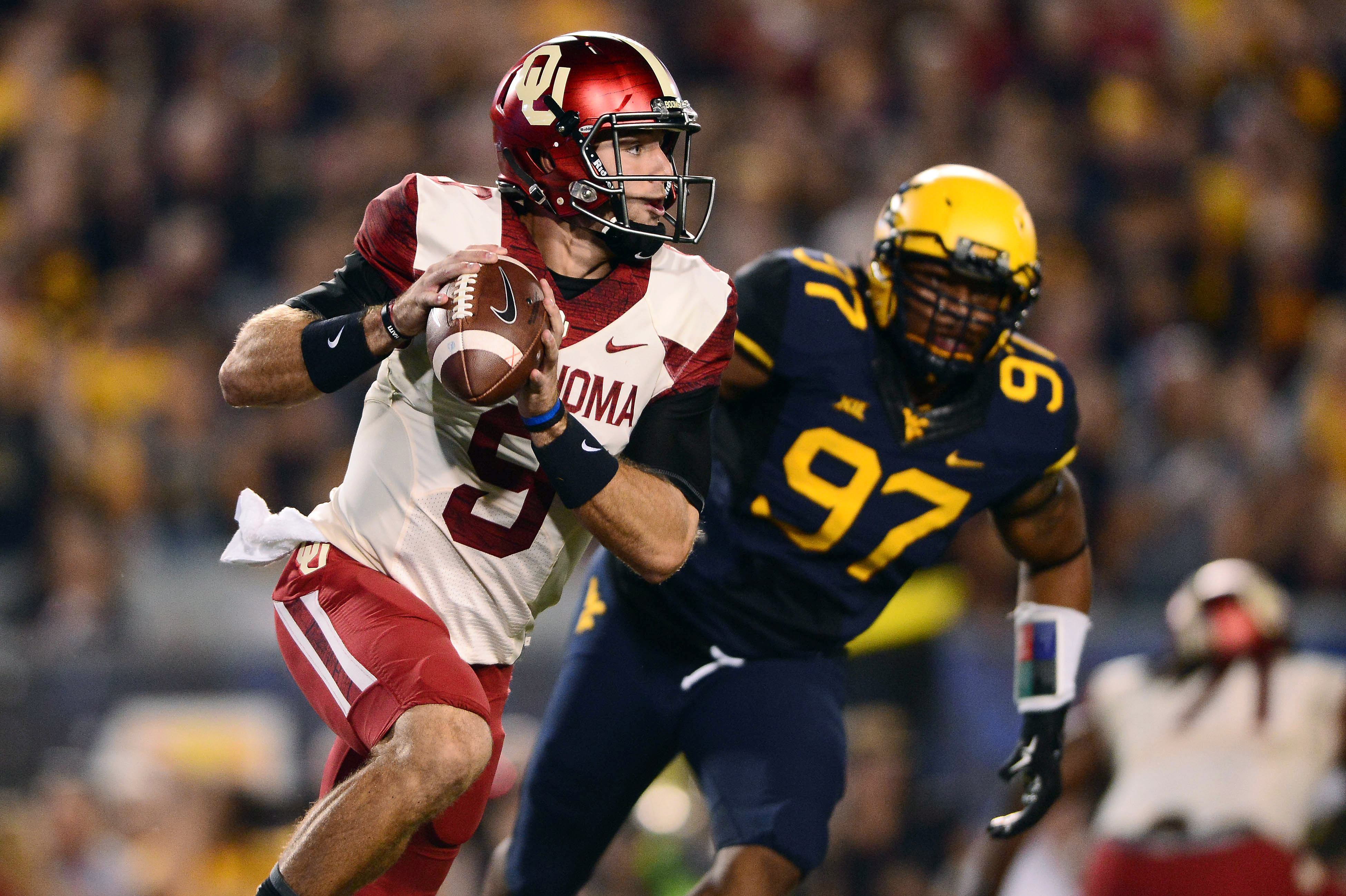 Oklahoma Sooners quarterback Trevor Knight (9) is pressured by West Virginia Mountaineers defensive lineman Noble Nwachukwu (97) during the first quarter at Milan Puskar Stadium. (Andrew Weber-USA TODAY Sports)