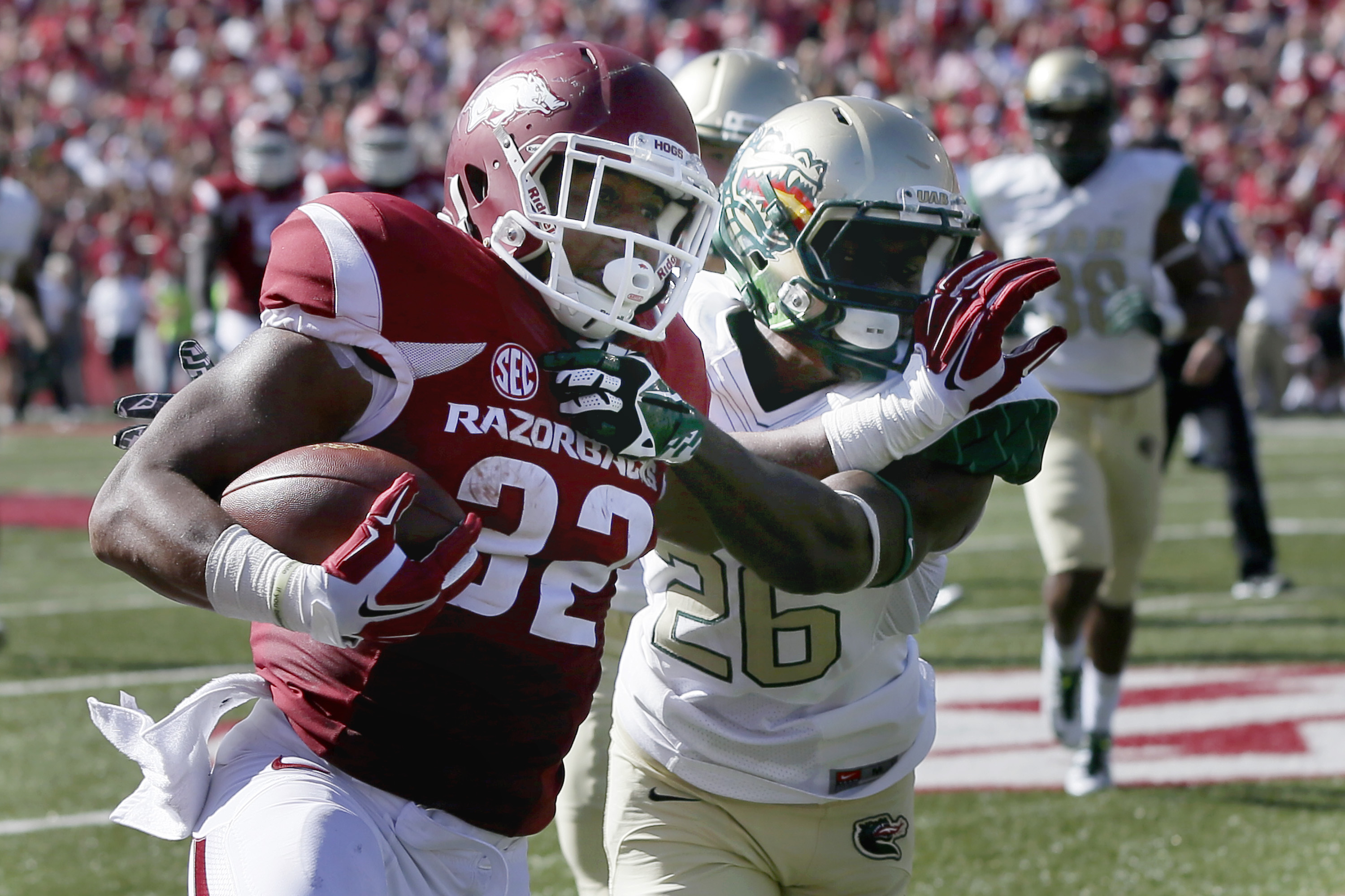 Arkansas running back Jonathan Williams (32) pushes UAB cornerback Rolan Milligan (26) away in the first half of an NCAA college football game in Fayetteville, Ark., Saturday, Oct. 25, 2014. (AP Photo/Danny Johnston)