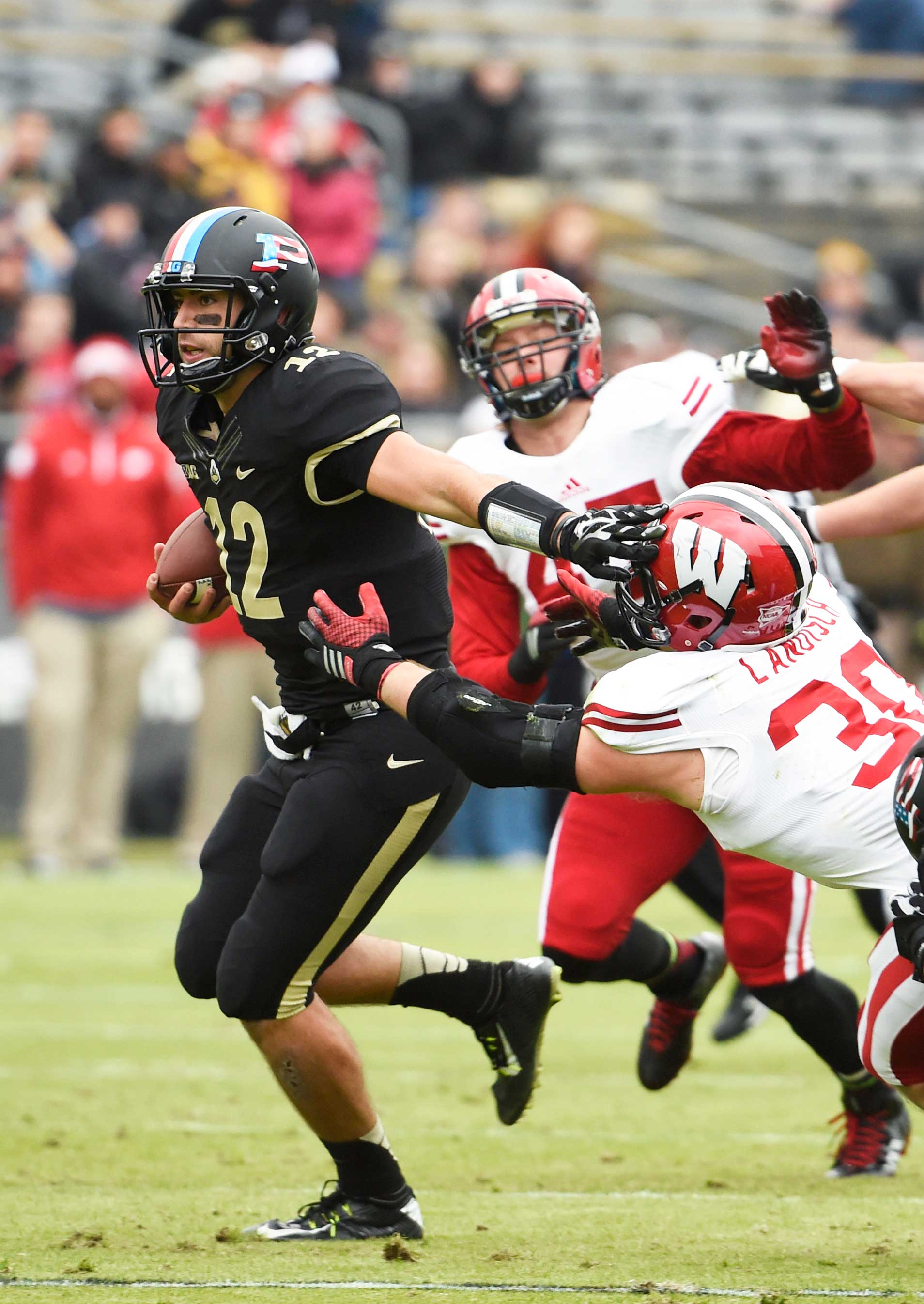 Purdue Boilermakers quarterback Austin Appleby (12) runs through the tackle of Wisconsin Badgers linebacker Derek Landisch (30) in the first half at Ross Ade Stadium. (Sandra Dukes-USA TODAY Sports)