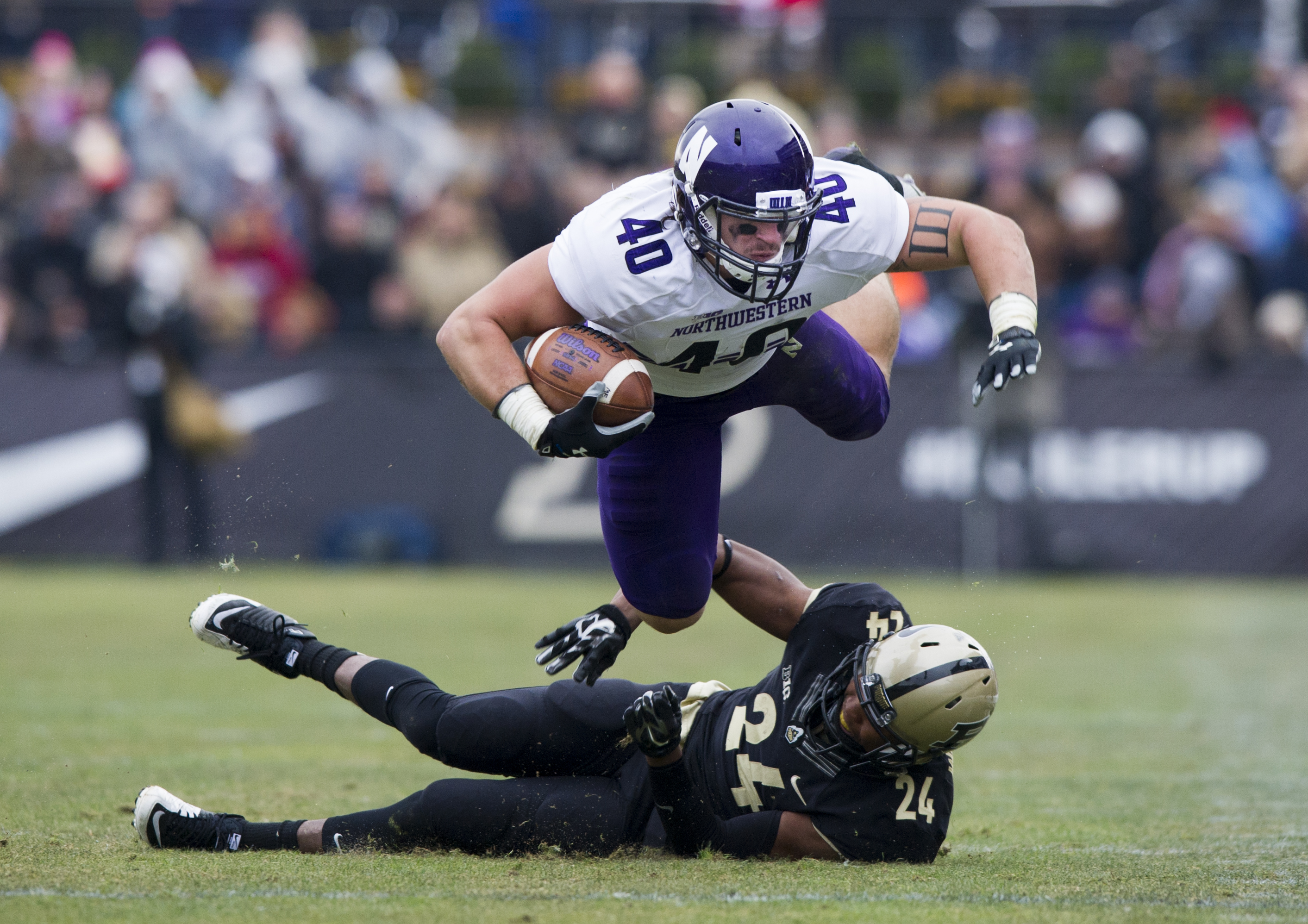 Northwestern's Dan Vitale (40) is tripped up by Purdue's Frankie Williams (24) as he runs the ball during the first half of an NCAA college football game, Saturday, Nov. 22, 2014, in West Lafayette, Ind. (AP Photo/Doug McSchooler)
