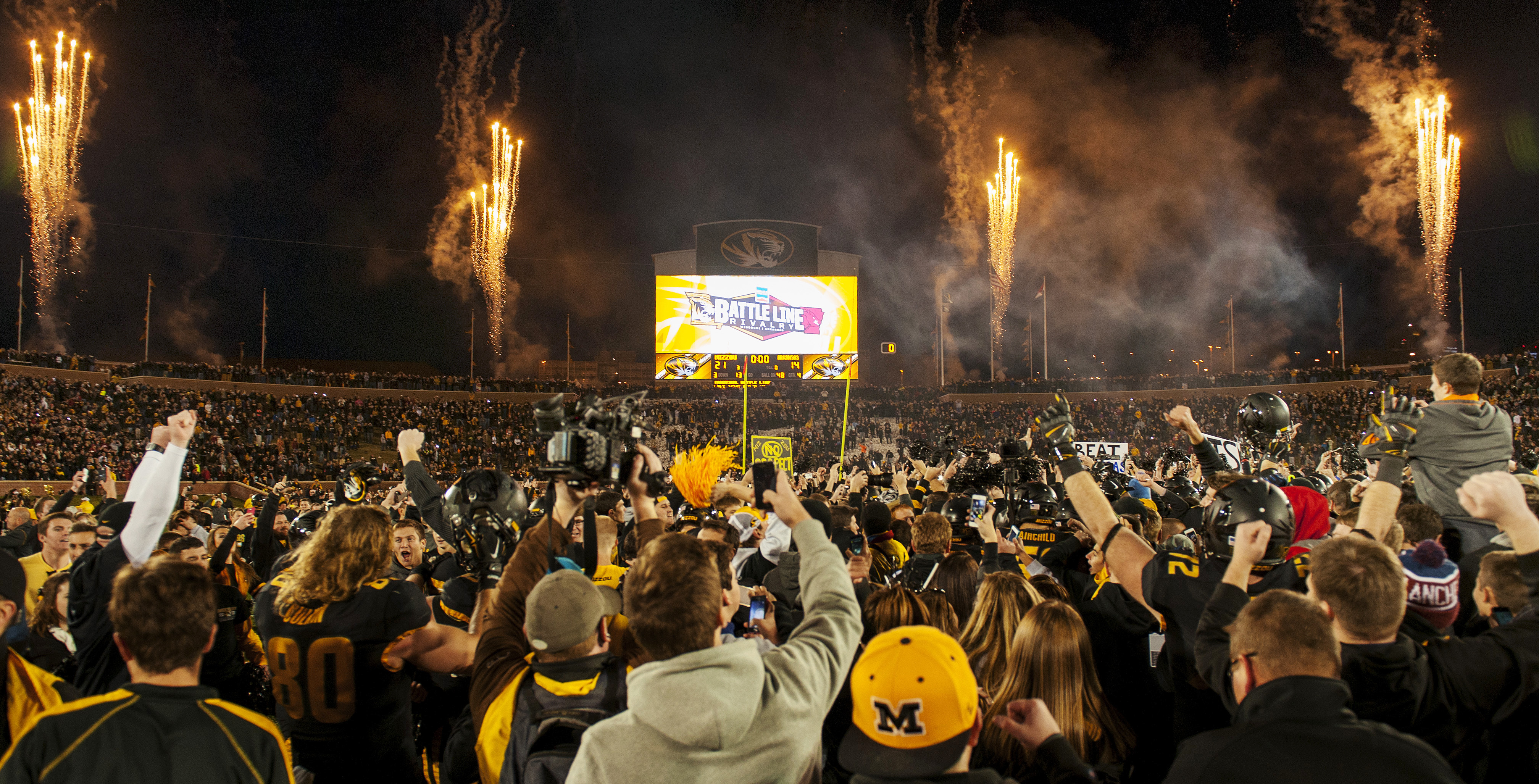 Missouri fans rush the field and celebrate after the team's  21-14 victory over Arkansas in an NCAA college football game Friday, Nov. 28, 2014, in Columbia, Mo. Missouri won 21-14. (AP Photo/L.G. Patterson)