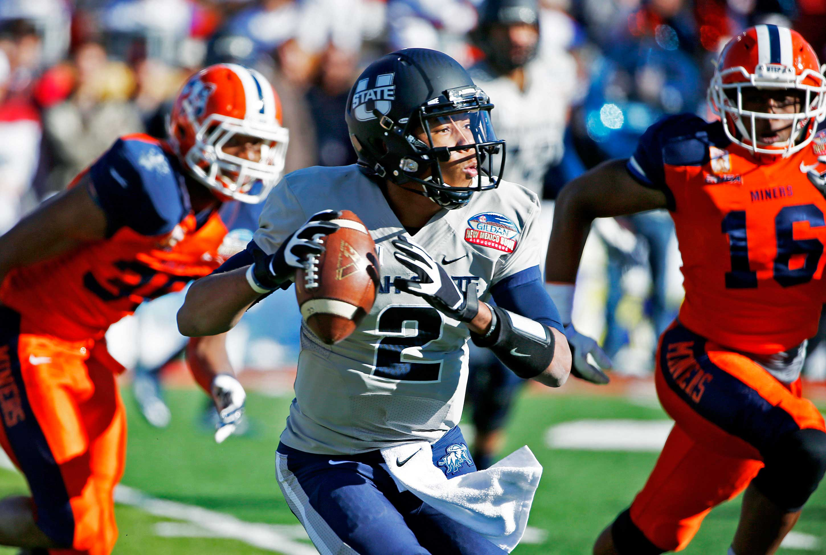 Utah State's Kent Myers (2) looks to pass the ball as he is chased by UTEP's Nick Usher, left, and Alvin Jones (16) during the first half of the New Mexico Bowl NCAA college football game Saturday, Dec. 20, 2014, in Albuquerque, N.M. (AP Photo/Ross D. Franklin)