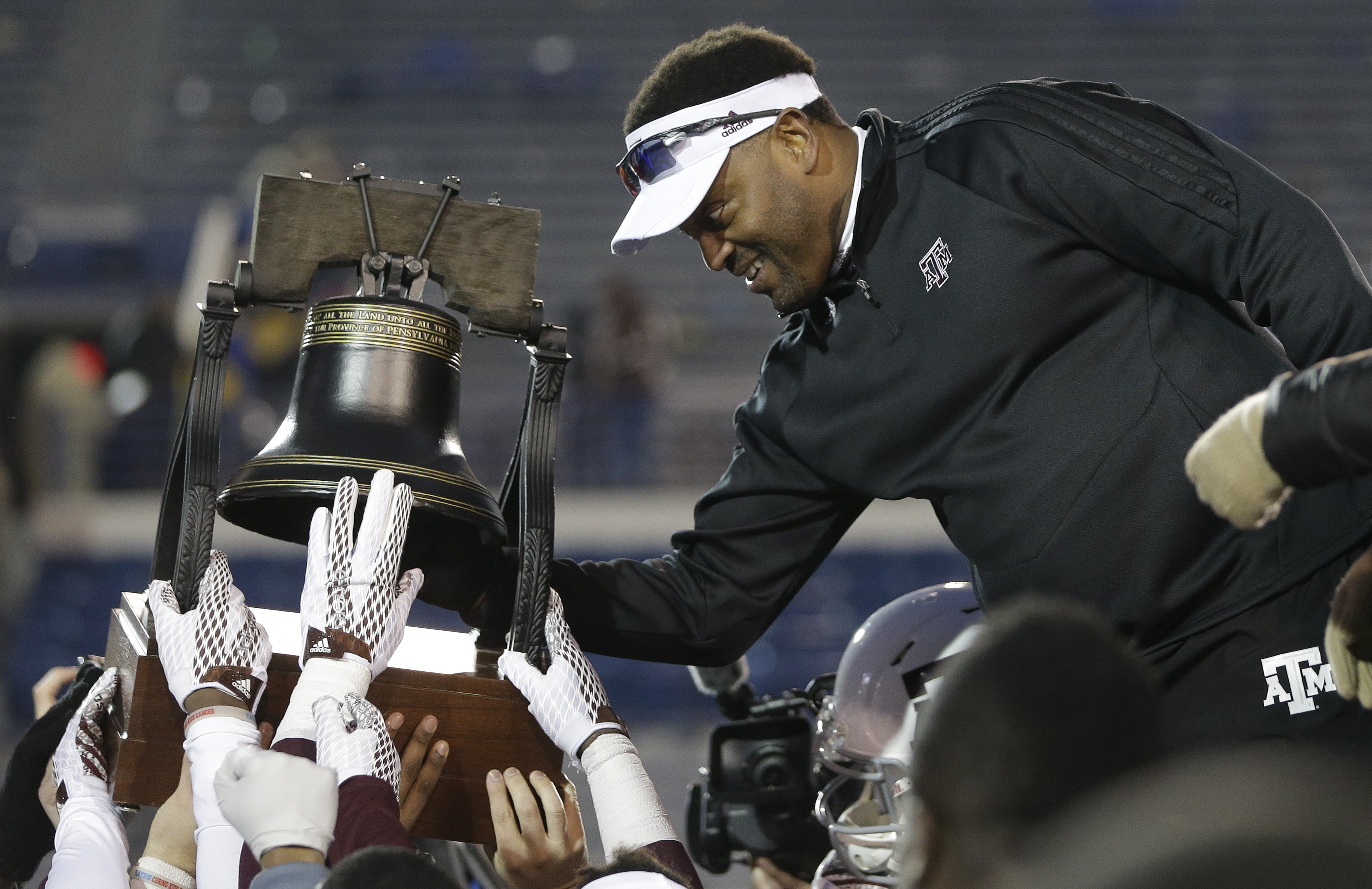 Texas A&M head coach Kevin Sumlin rings the Liberty Bell trophy after beating West Virginia in the Liberty Bowl NCAA college football game Monday, Dec. 29, 2014, in Memphis, Tenn. Texas A&M won 45-37. (AP Photo/Mark Humphrey)