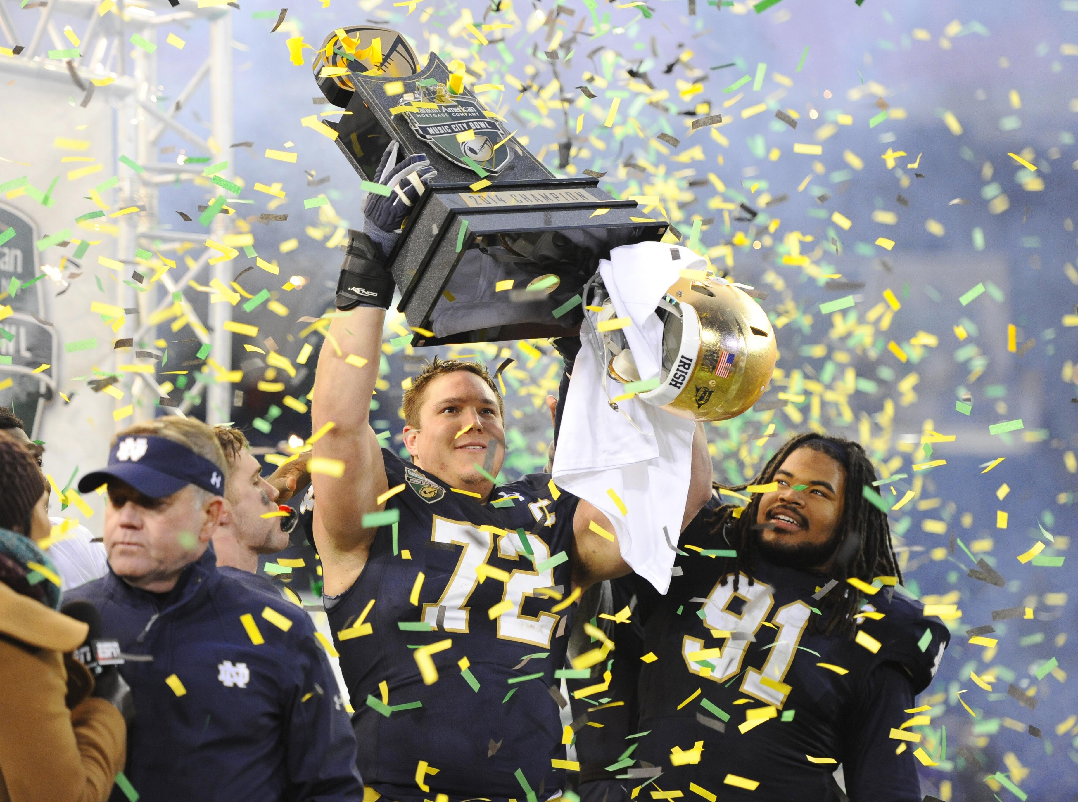 Dec 30, 2014; Nashville, TN, USA; Notre Dame Fighting Irish offensive lineman Nick Martin (72) and defensive lineman Sheldon Day (91) celebrate after winning the game against the LSU Tigers in the Music City Bowl at LP Field. Notre Dame won 31-28. (Christopher Hanewinckel-USA TODAY Sports)