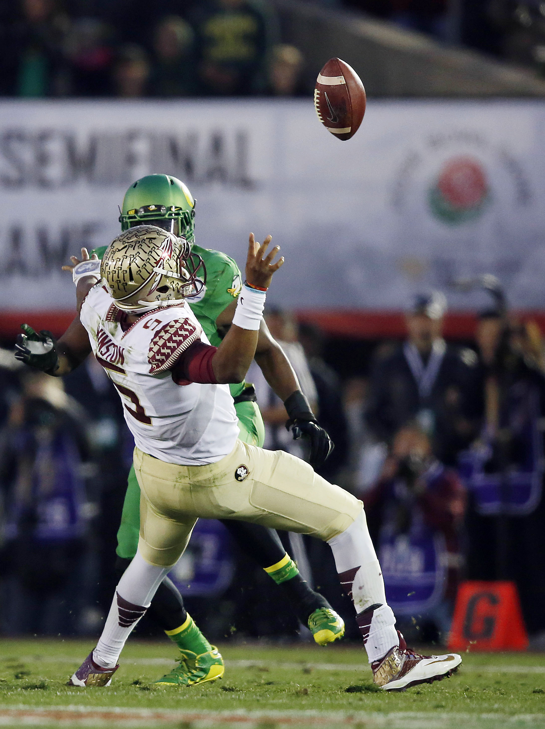 Oregon linebacker Tony Washington (91) forces a fumble by Florida State quarterback Jameis Winston (5), and then returned the ball for a touchdown in the Rose Bowl NCAA college football playoff semifinal, Thursday, Jan. 1, 2015 in Pasadena, Calif. Oregon won 59-20. (AP Photo/Doug Benc)