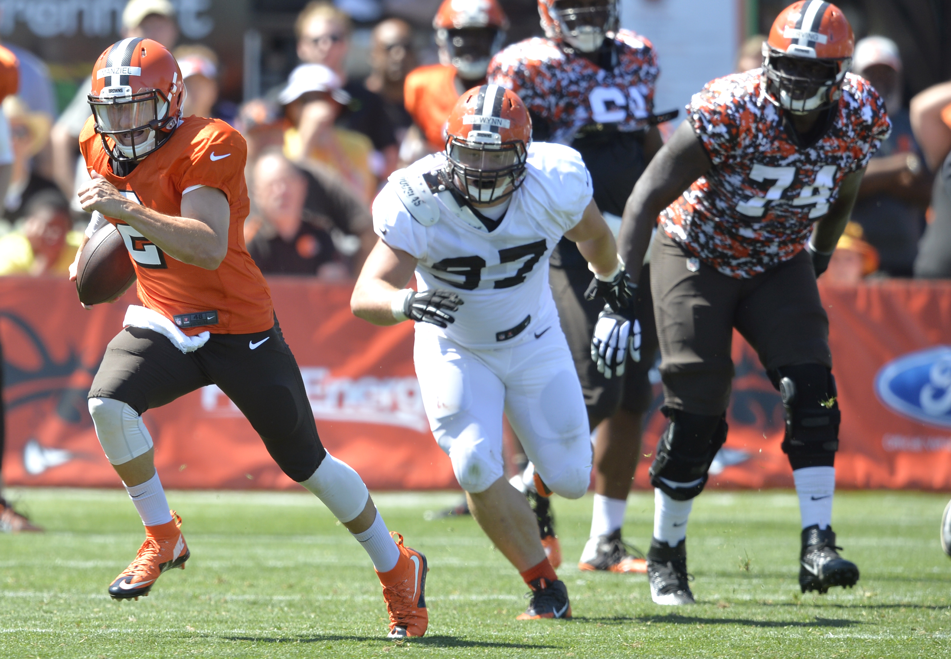 Cleveland Browns defensive tackle Dylan Wynn (97) chases quarterback Johnny Manziel (2) during practice at NFL football training camp, Tuesday, Aug. 4, 2015, in Berea, Ohio. (AP Photo/David Richard)