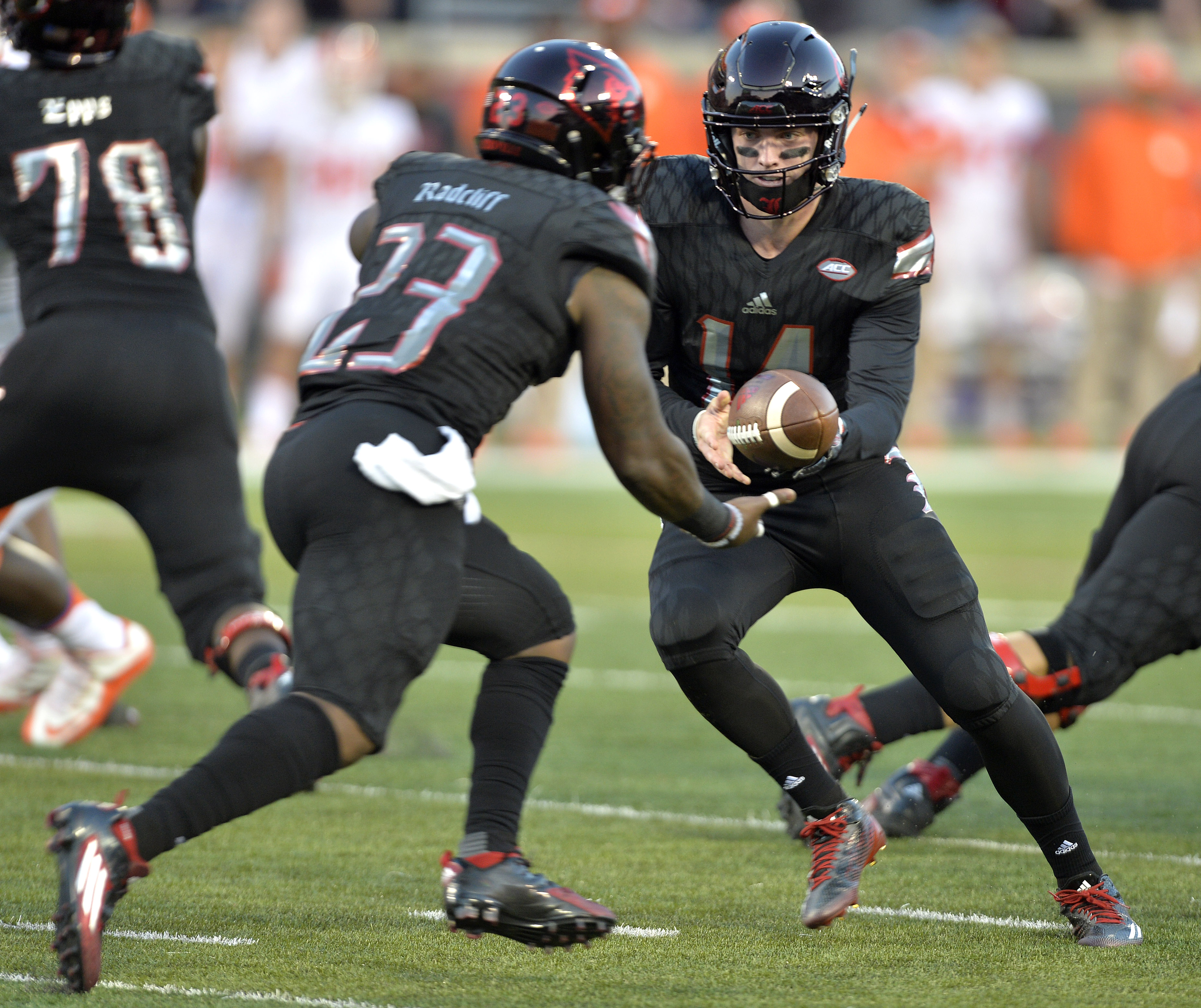 Louisville quarterback Kyle Bolin, right, hands the ball off to Brandon Radcliff during the first half of an NCAA college football game against Clemson in Louisville, Ky., Thursday, Sept. 17, 2015. (AP Photo/Timothy D. Easley)