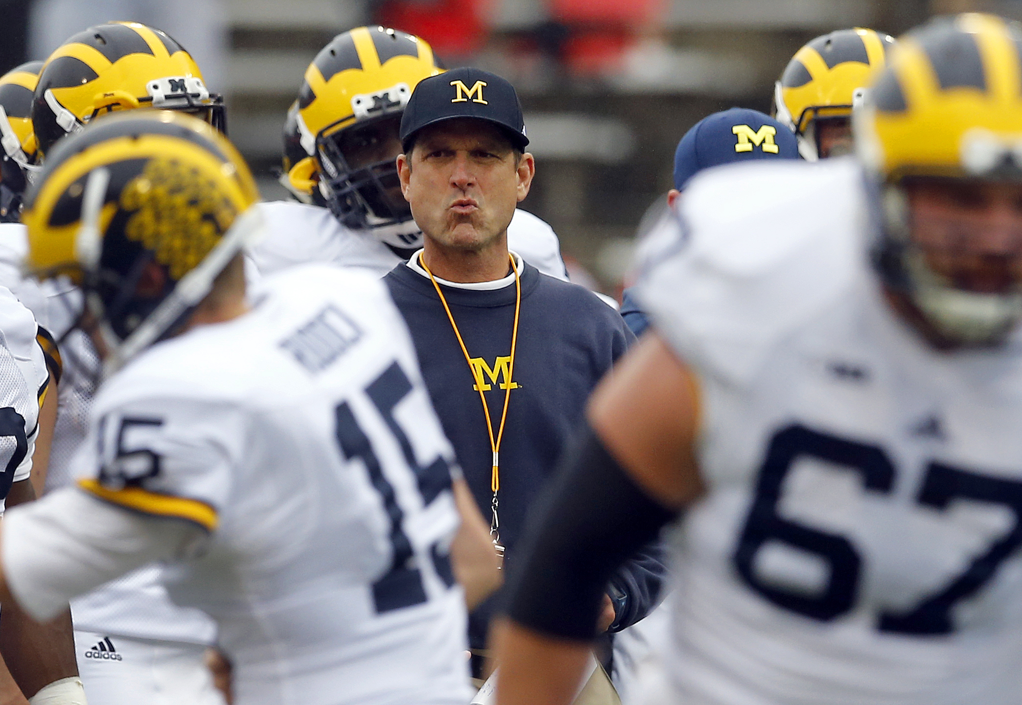 Michigan head coach Jim Harbaugh watches his players warm up before an NCAA college football game against Maryland, Saturday, Oct. 3, 2015, in College Park, Md. (AP Photo/Patrick Semansky)