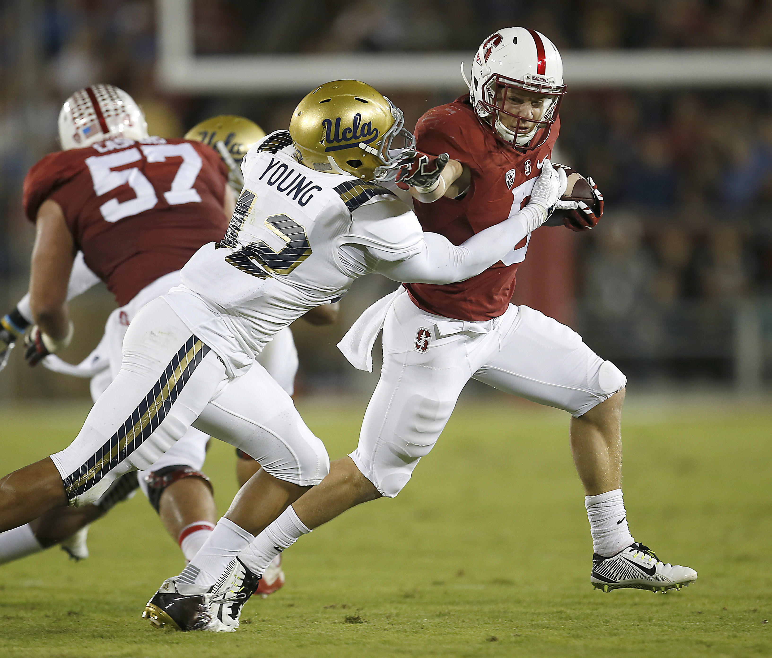 Stanford running back Christian McCaffrey (5) stiff-arms UCLA linebacker Kenny Young (42) during the first half of an NCAA college football game Thursday, Oct. 15, 2015, Stanford, Calif. (AP Photo/Tony Avelar)