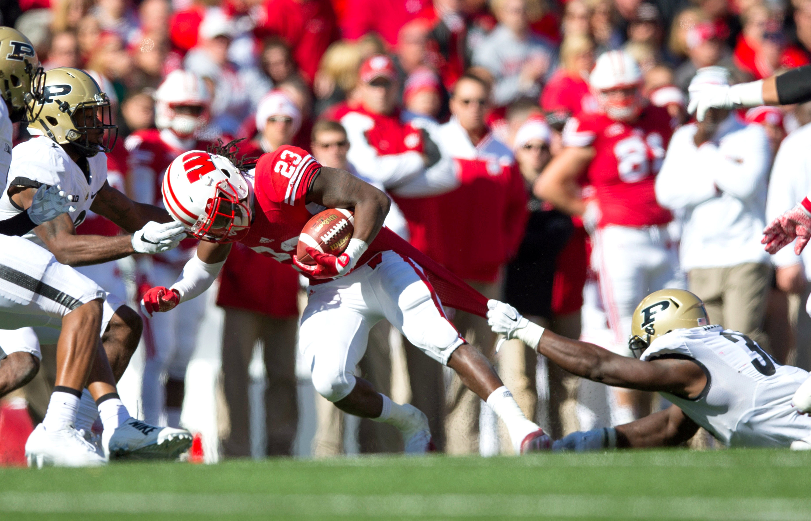 Oct 17, 2015; Madison, WI, USA; Wisconsin Badgers running back Dare Ogunbowale (23) rushes with the football as Purdue Boilermakers linebacker Danny Ezechukwu (36) defends during the third quarter at Camp Randall Stadium.  Wisconsin won 24-7.