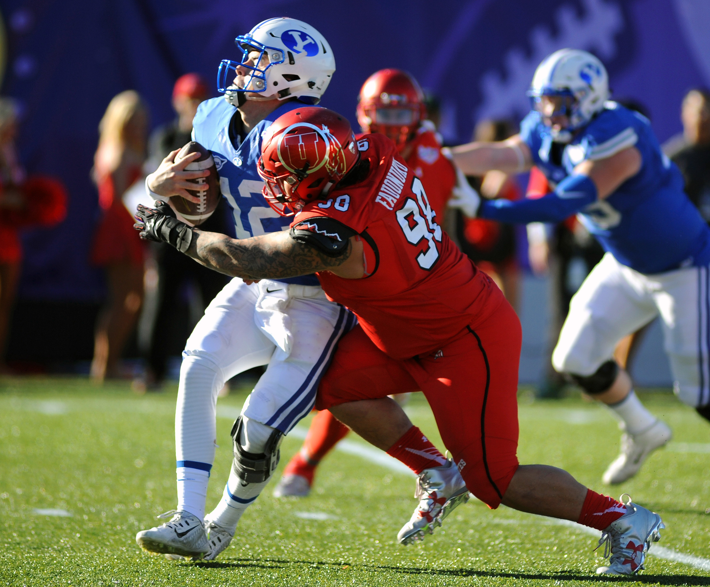 Dec 19, 2015; Las Vegas, NV, USA; BYU Cougars quarterback Tanner Magnum (12) is sacked for a loss by Utah Utes defensive tackle Viliseni Fauonuku (98) in the Las Vegas Bowl at Sam Boyd Stadium. (Stephen R. Sylvanie/USA TODAY Sports)