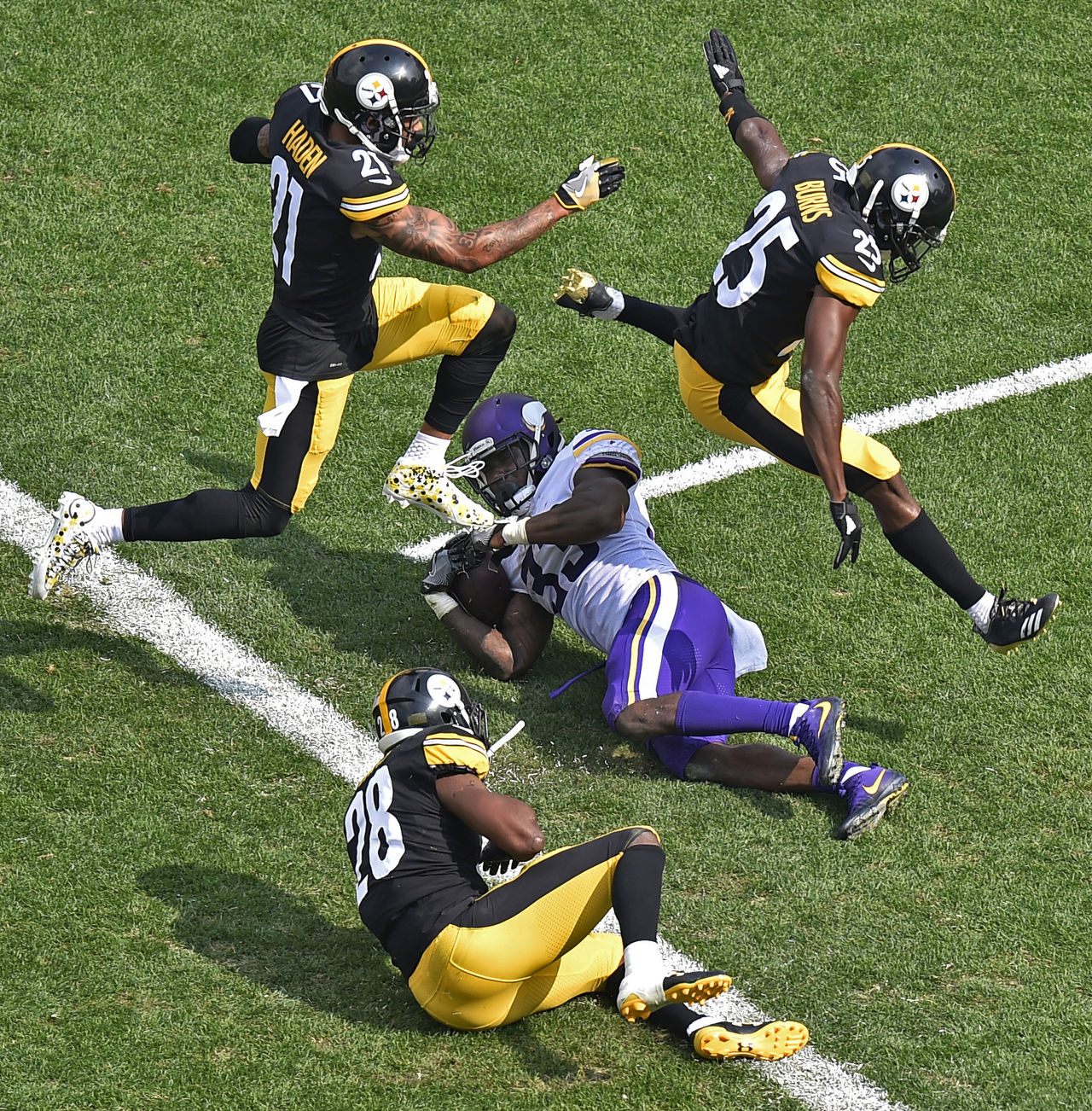 Pittsburgh Steelers cornerback Joe Haden (21) and Artie Burns (25) leap over Minnesota Vikings running back Dalvin Cook (33) after he scored on a pass play from quarterback Case Keenum during the second half of an NFL football game in Pittsburgh, Sunday, Sept. 17, 2017.