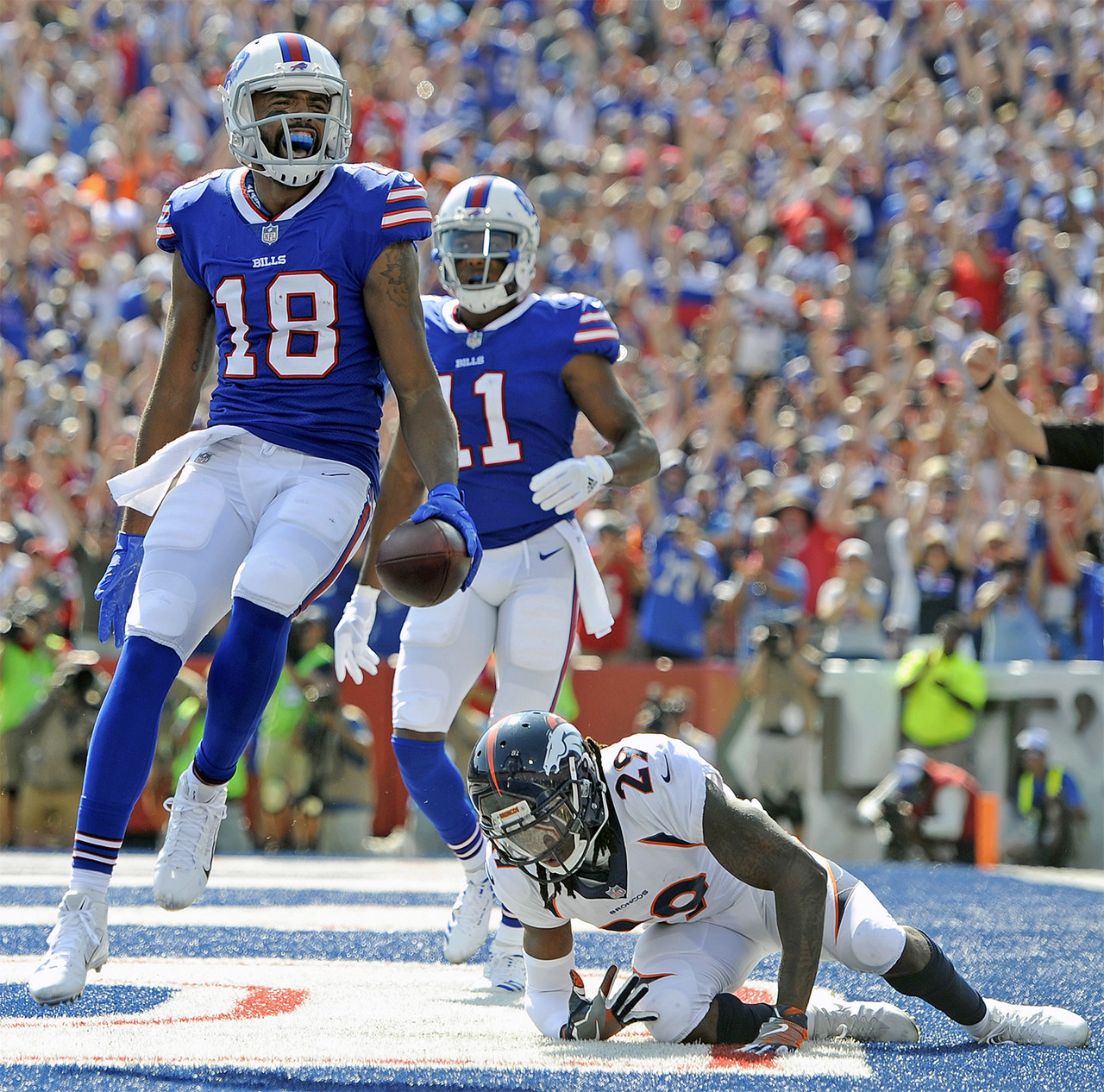 Buffalo Bills wide receiver Andre Holmes (18) celebrates after catching a touchdown pass from quarterback Tyrod Taylor, not pictured, as Denver Broncos free safety Bradley Roby (29) is slow to get up during the first half of an NFL football game, Sunday, Sept. 24, 2017, in Orchard Park, N.Y.