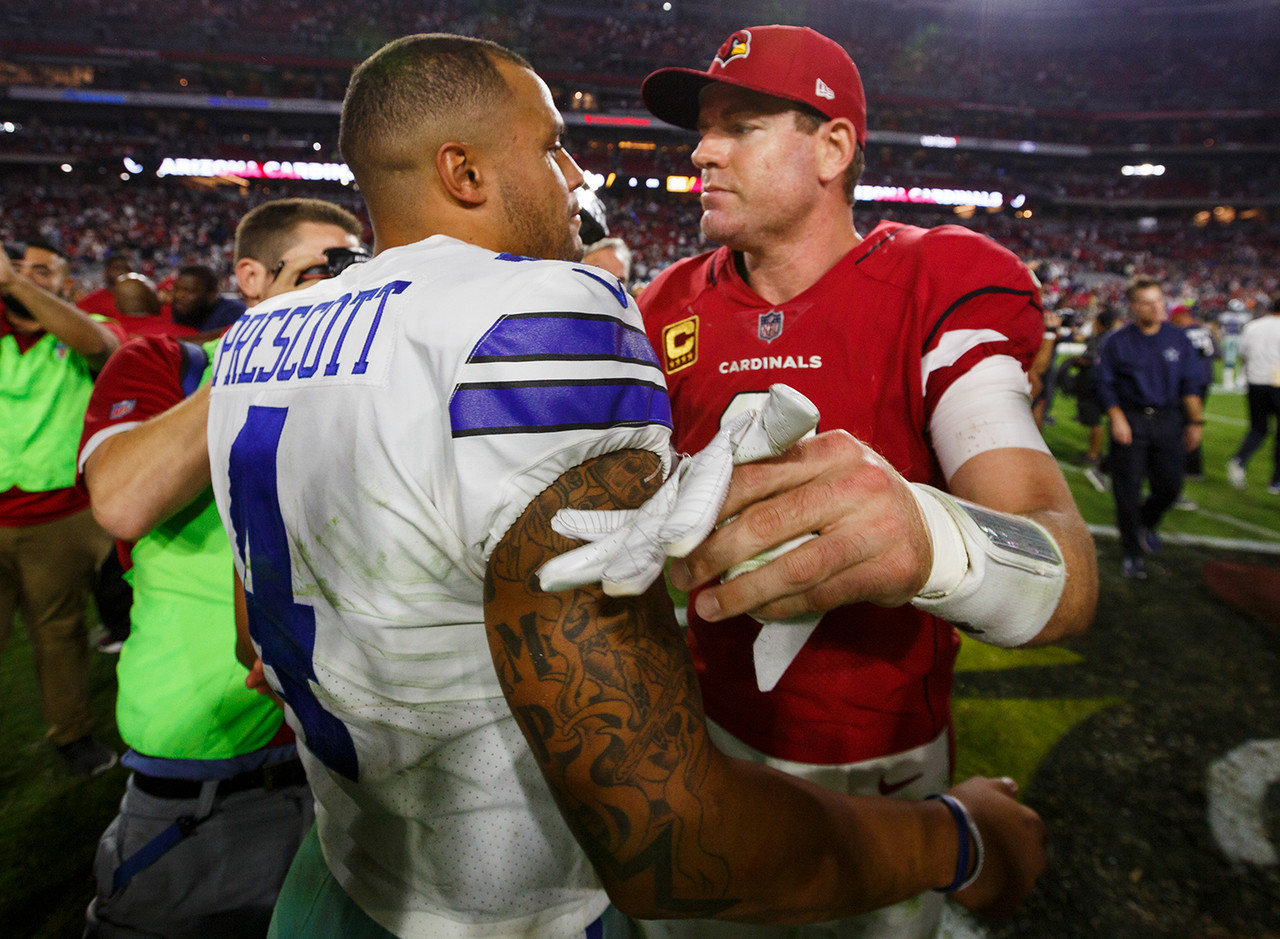 Dallas Cowboys quarterback Dak Prescott (4) and Arizona Cardinals quarterback Carson Palmer (3) meet after an NFL football game, Monday, Sept. 25, 2017, in Glendale, Ariz. The Cowboys defeated the Cardinals, 28-17.
