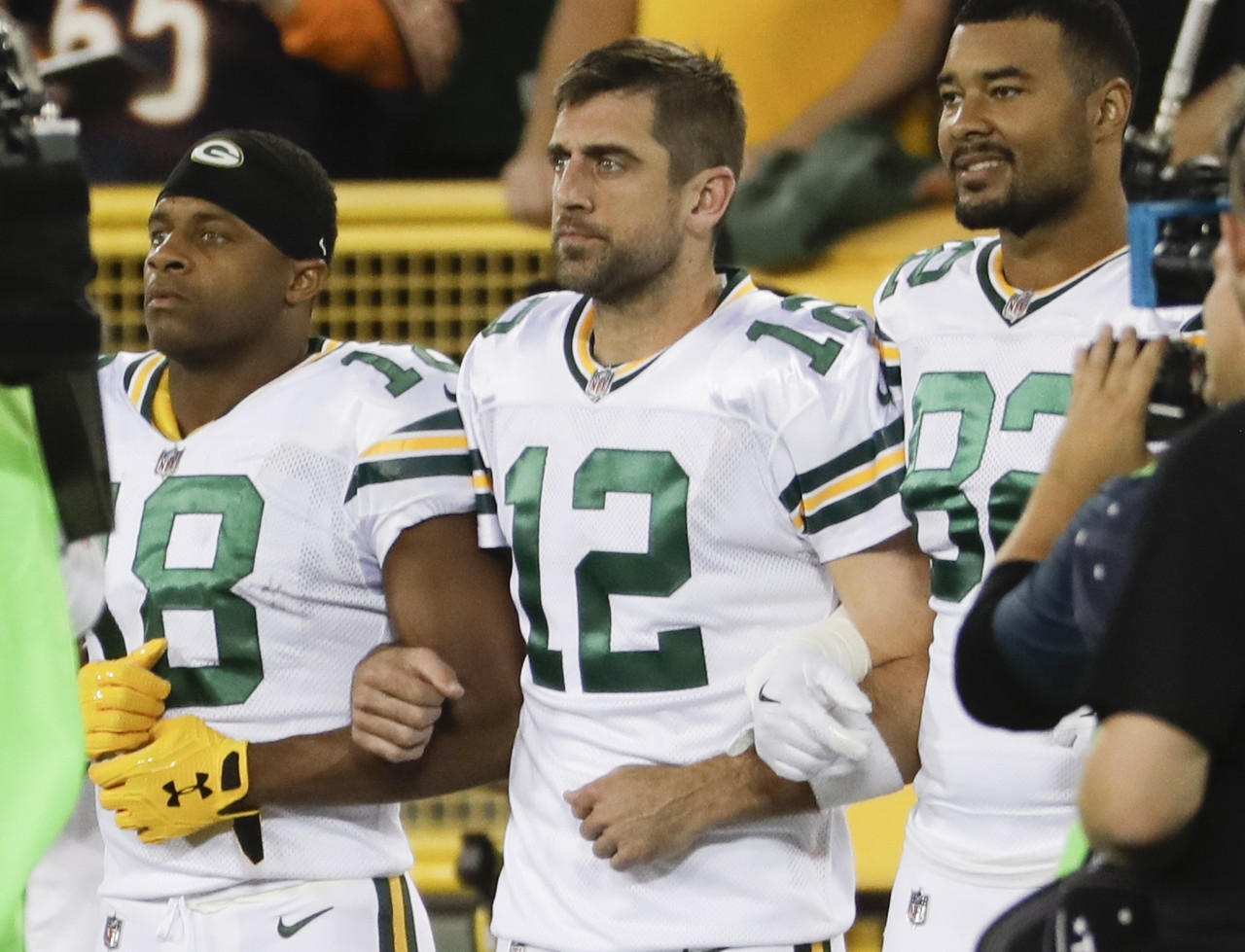 Green Bay Packers' Aaron Rodgers links arms with Richard Rodgers and Randall Cobb during the national anthem before an NFL football game against the Chicago Bears Thursday, Sept. 28, 2017, in Green Bay, Wis.