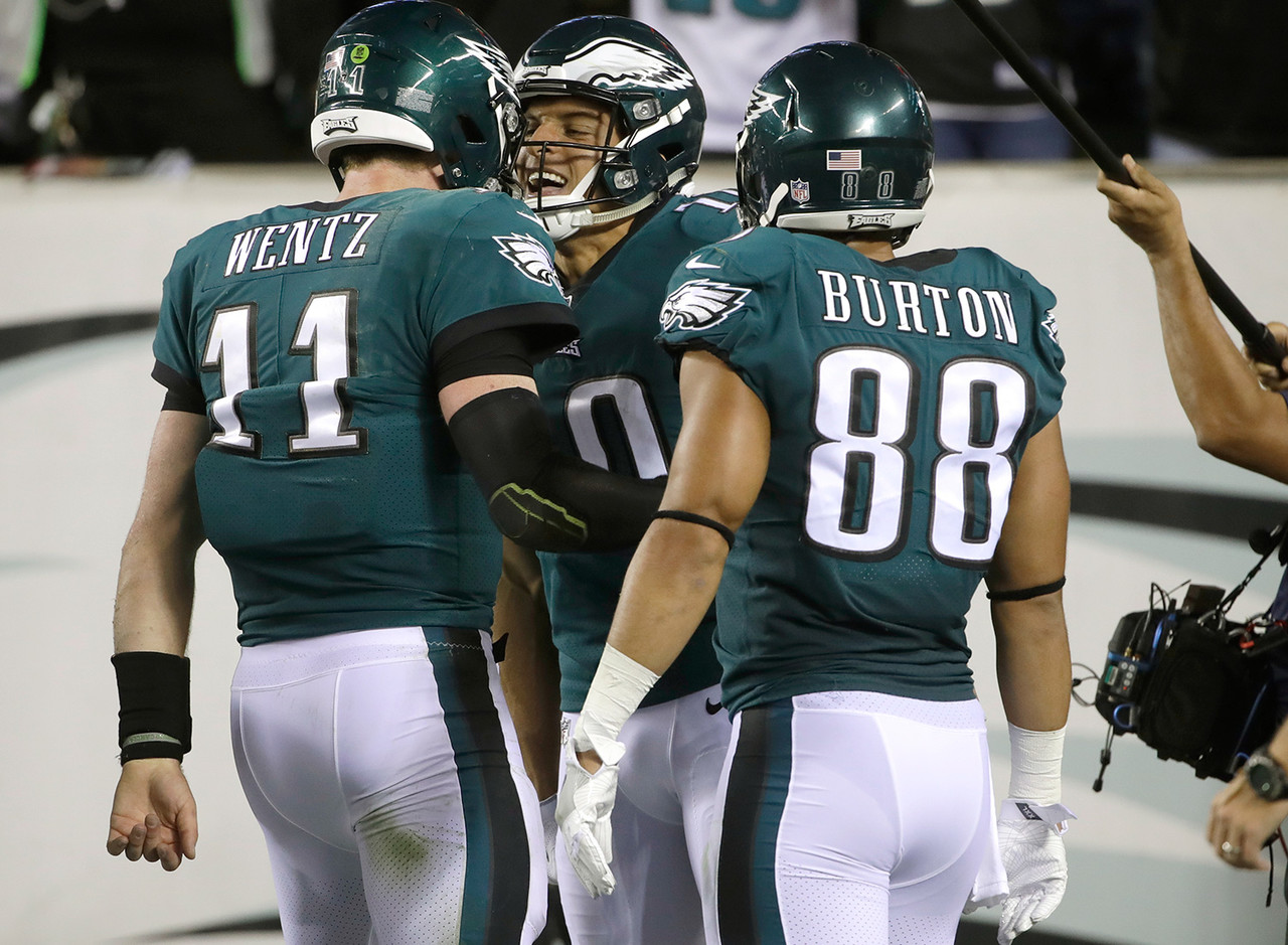 Philadelphia Eagles quarterback Carson Wentz (11) and Philadelphia Eagles wide receiver Mack Hollins (10) celebrate after they connected on a touchdown pass as teammate Trey Burton (88) looks on during the first half of an NFL football game against the Washington Redskins, Monday, Oct. 23, 2017, in Philadelphia.