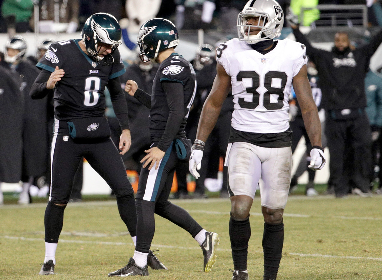 Philadelphia Eagles' Jake Elliott (4) and Donnie Jones (8) celebrate past Oakland Raiders' T.J. Carrie (38) after Elliott's field goal during the second half of an NFL football game, Monday, Dec. 25, 2017, in Philadelphia.