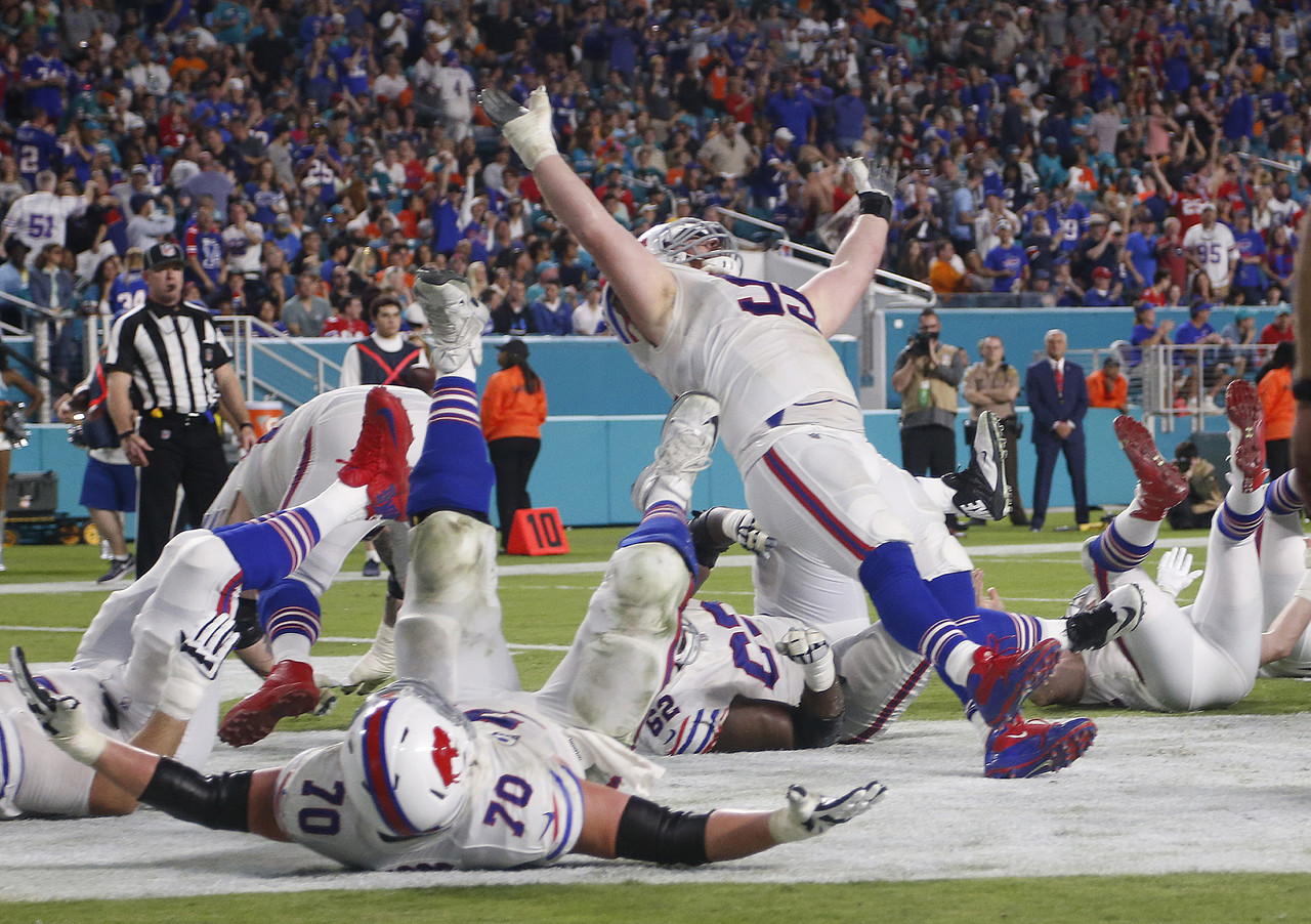 Buffalo Bills defensive tackle Kyle Williams (95) and a group of players fall to the ground in celebration after Williams scored a touchdown, during the second half of an NFL football game against the Miami Dolphins, Sunday, Dec. 31, 2017, in Miami Gardens, Fla.