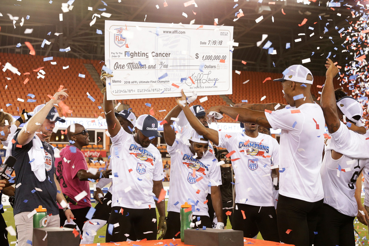 Team Fighting Cancer celebrate while holding up their million-dollar check as confetti falls after they win the American Flag Football League (AFFL) U.S. Open of Football Ultimate Championship.