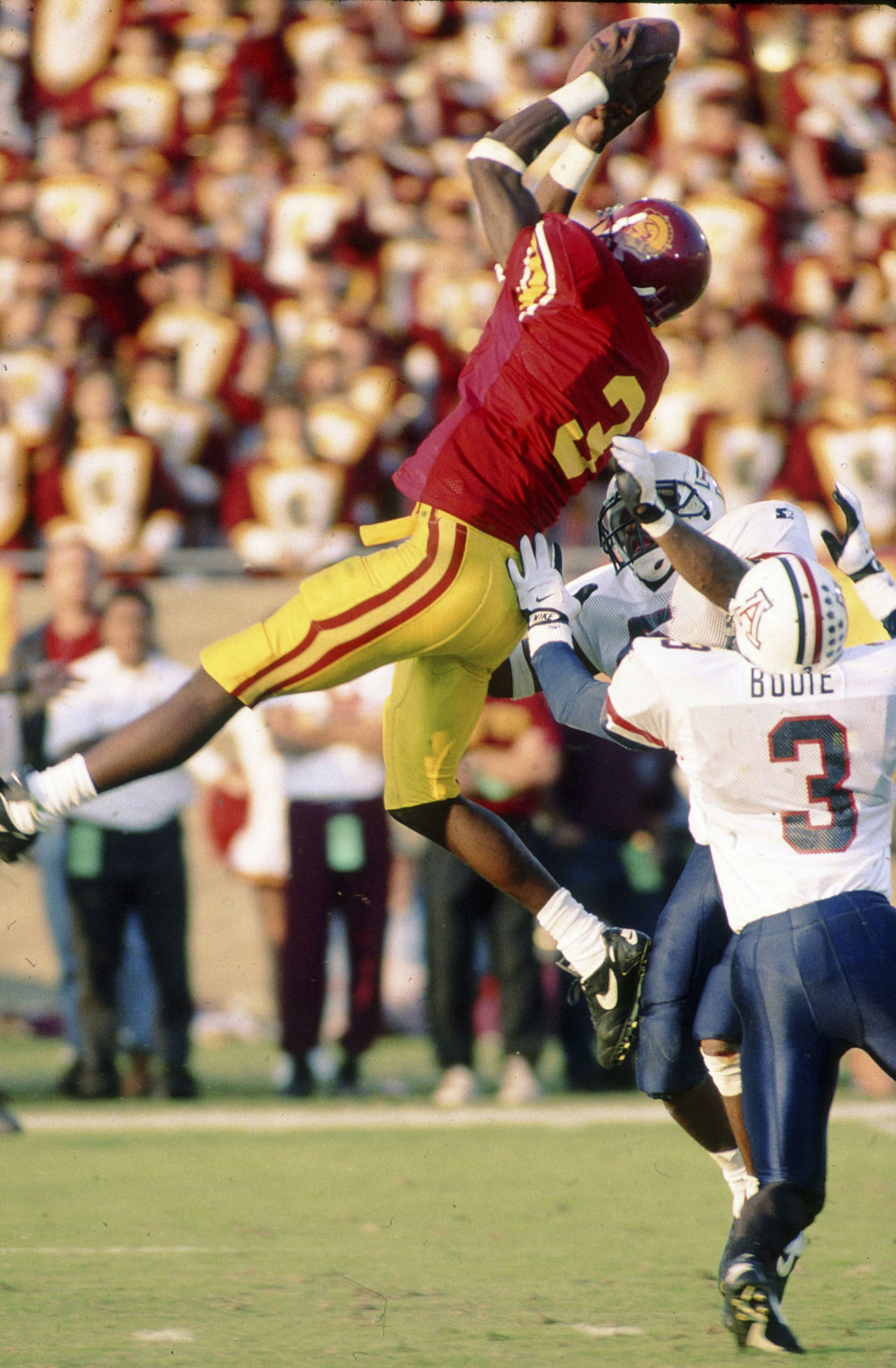 USC Trojans wide receiver Keyshawn Johnson (3) leaps to make a reception in front of Arizona Cardinals safety Tony Bouie (3) during an NCAA game in Los Angeles on November 12, 1994.  The Trojans defeated the Wildcats 45-28.