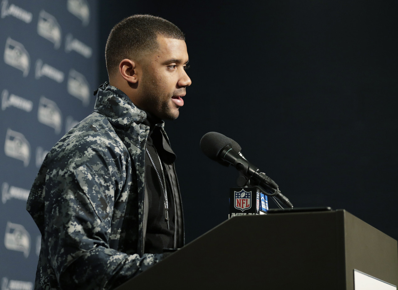 Seattle Seahawks quarterback Russell Wilson wears a camouflage jacket, and a cross and military style dog tag as he talks to reporters following an NFL football game against the Green Bay Packers, Thursday, Nov. 15, 2018, in Seattle.